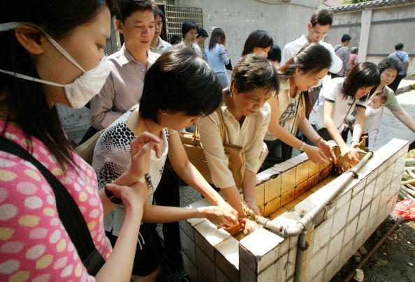 People wait in line to clean their hands May 1, 2003.