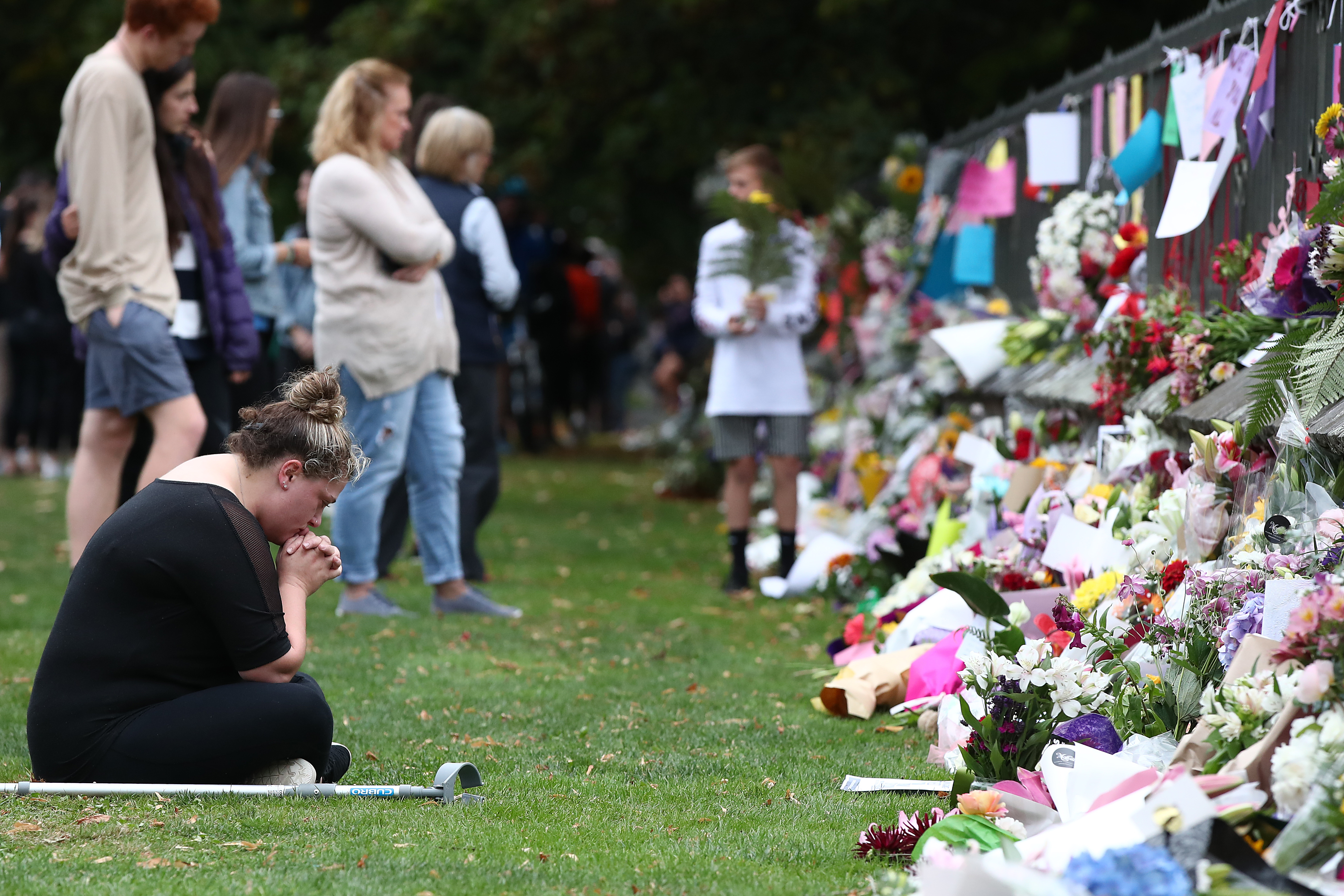 Mourners leave messages and flowers for the Christchurch mosque victims outside the city's Botanic Gardens