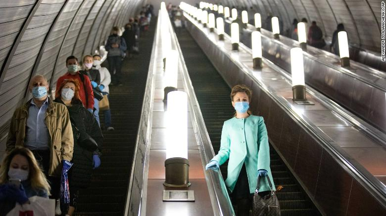 People wear face masks and gloves on a subway escalator in Moscow on Tuesday.