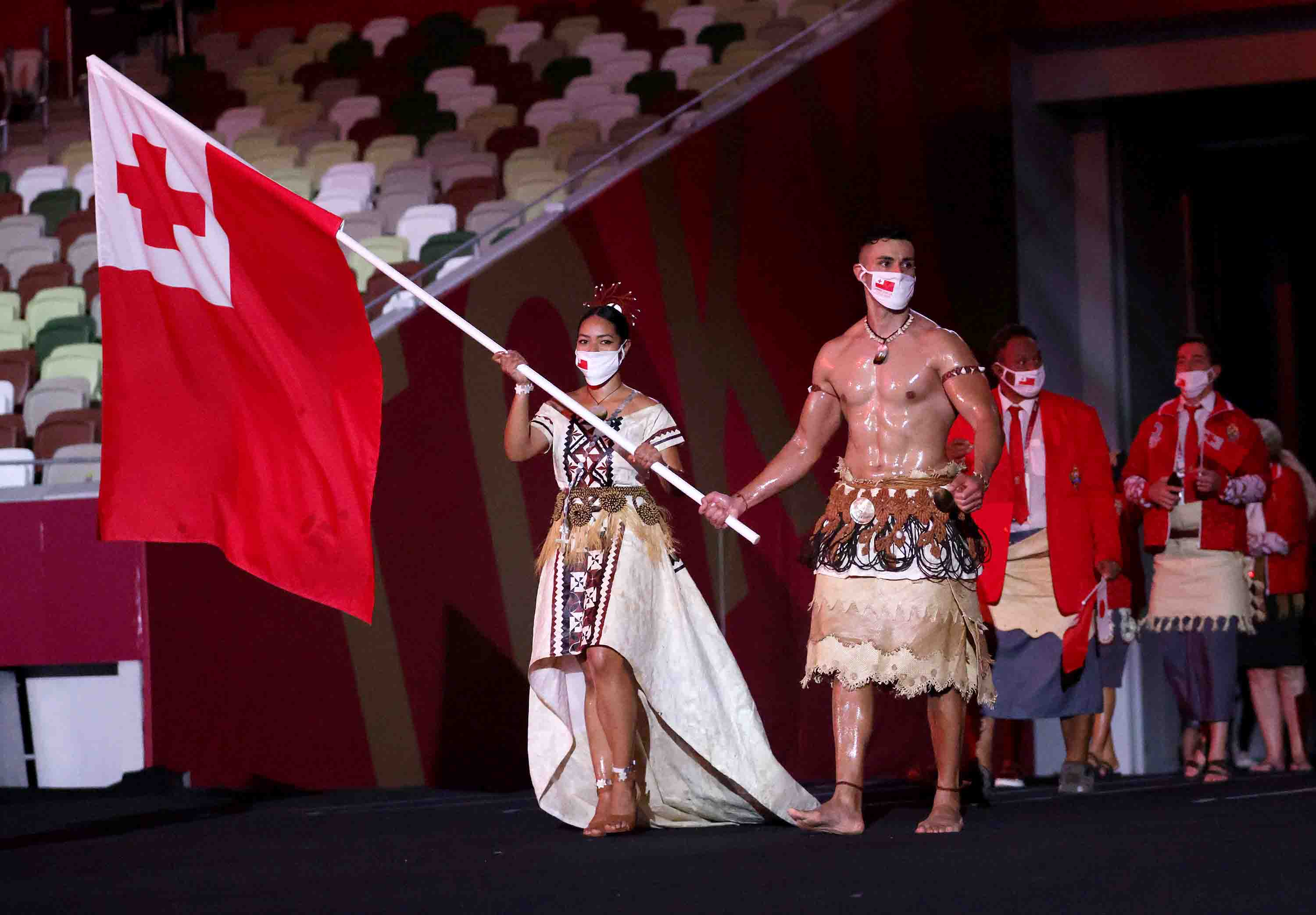 Pita Taufatofua, right, of Team Tonga carries the flag with Malia Paseka as they lead their team out during the Opening Ceremony.