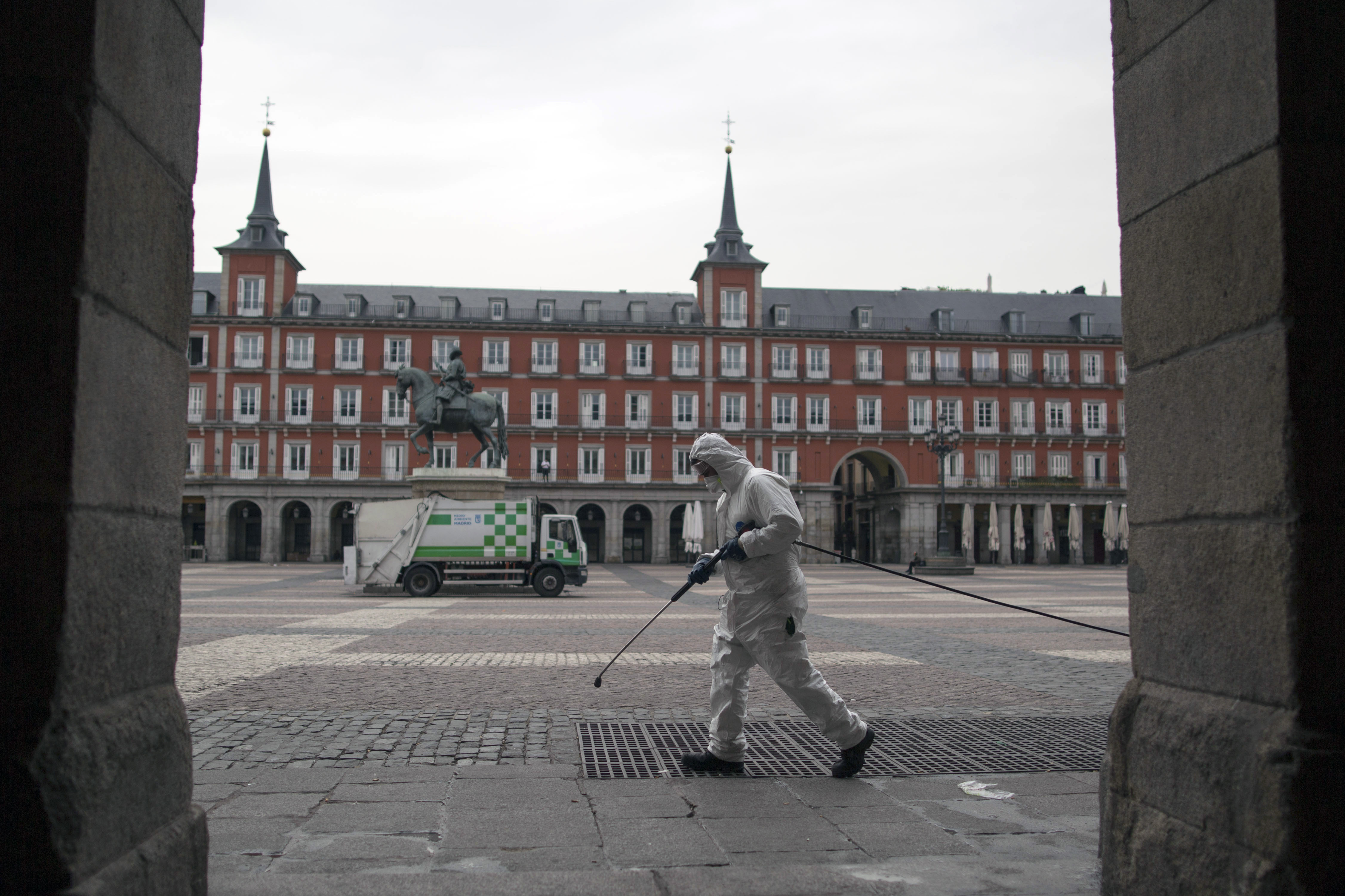 A worker cleans the pavement of Plaza Mayor square in Madrid, Spain, on March 18.