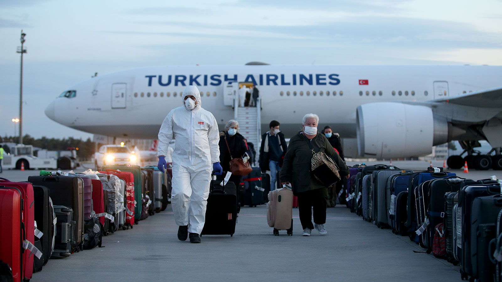 Officials accompany passengers to conduct a health check-up at Esenboga airport in Ankara, Turkey on April 20.