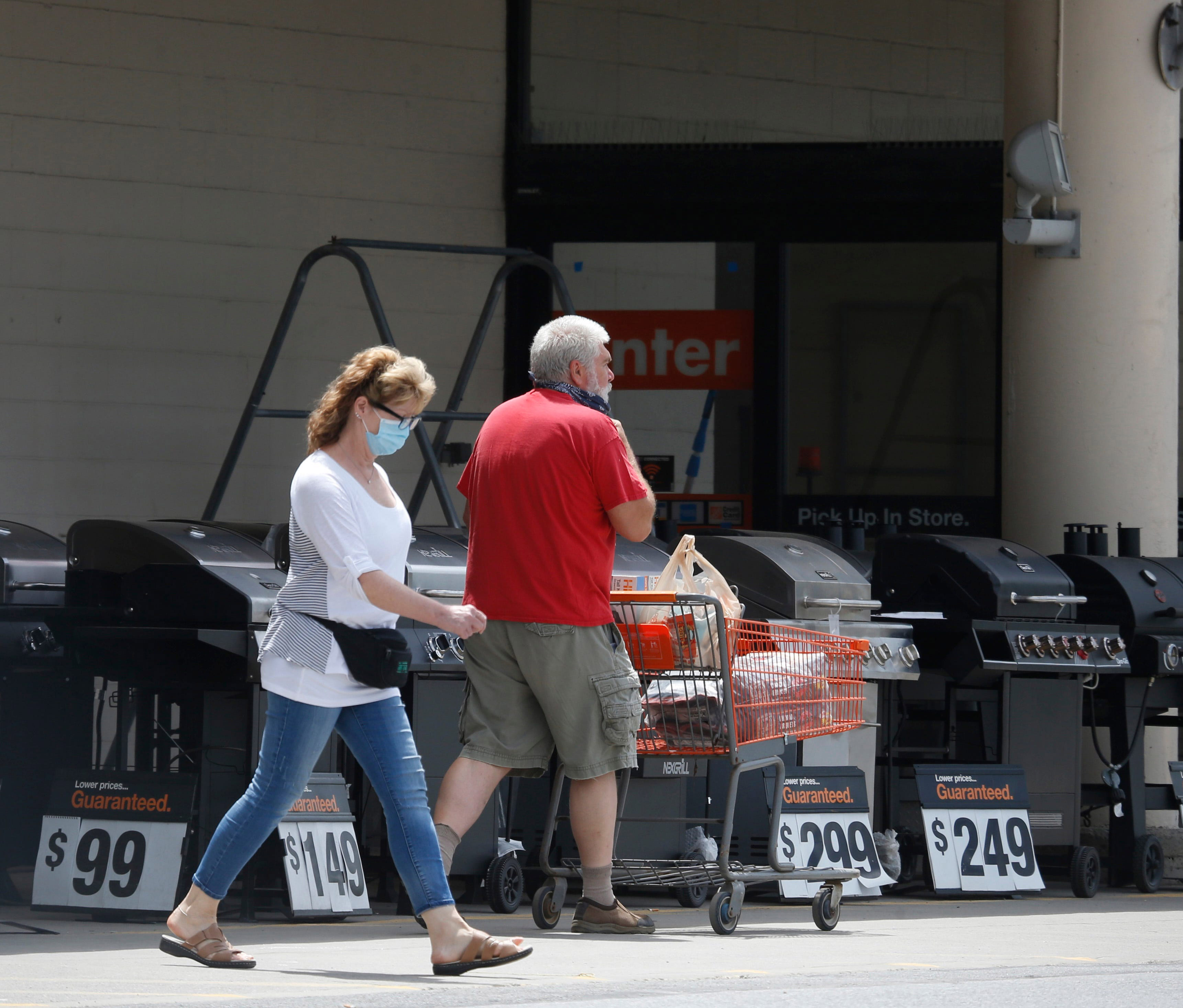 Customers walk in the parking lot of the Home Depot in Wappingers Falls, New York, on July 1.