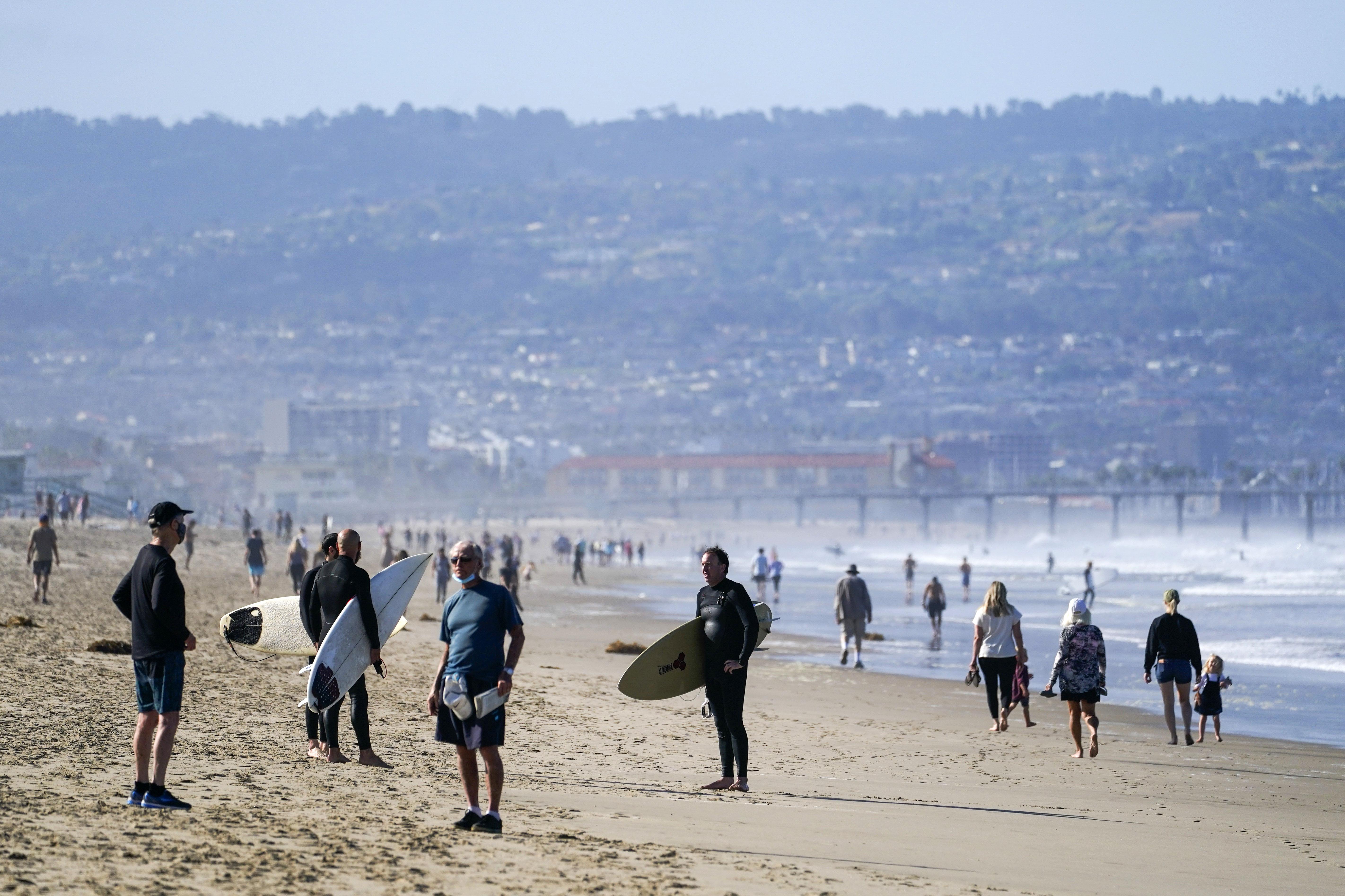 People walk on the sand in Manhattan Beach, California, on May 13.