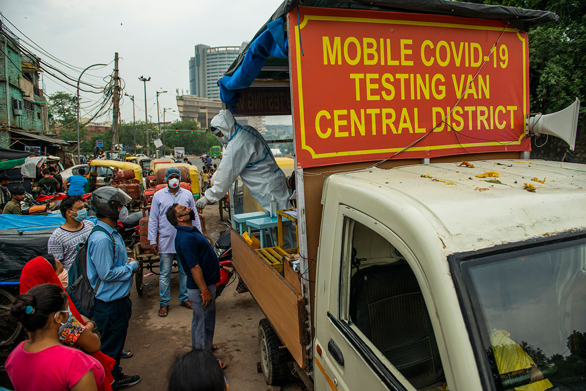 A health worker on a mobile testing van takes a nasal swab from a man in New Delhi, India on August 5.