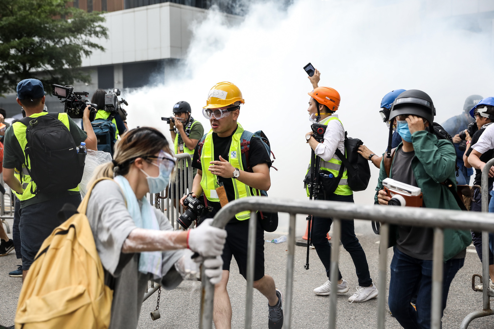 Protesters and members of the media react after police fired tear gas.
