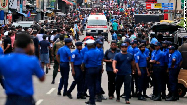 Sri Lankan police officers clear the road as an ambulance drives through carrying victims of the church blasts in Colombo, Sri Lanka on April 21, 2019.