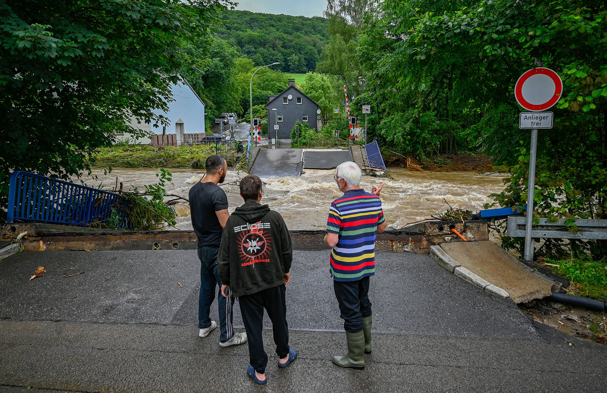 People look at a railway crossing that was destroyed by the flooding in Priorei, Germany.