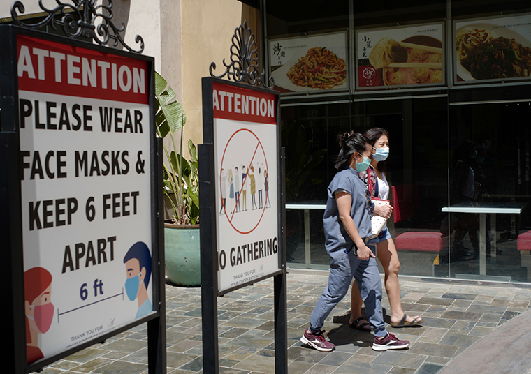 Customers wear face masks in an outdoor mall with closed business amid the COVID-19 pandemic in Los Angeleson June 11, 2021.