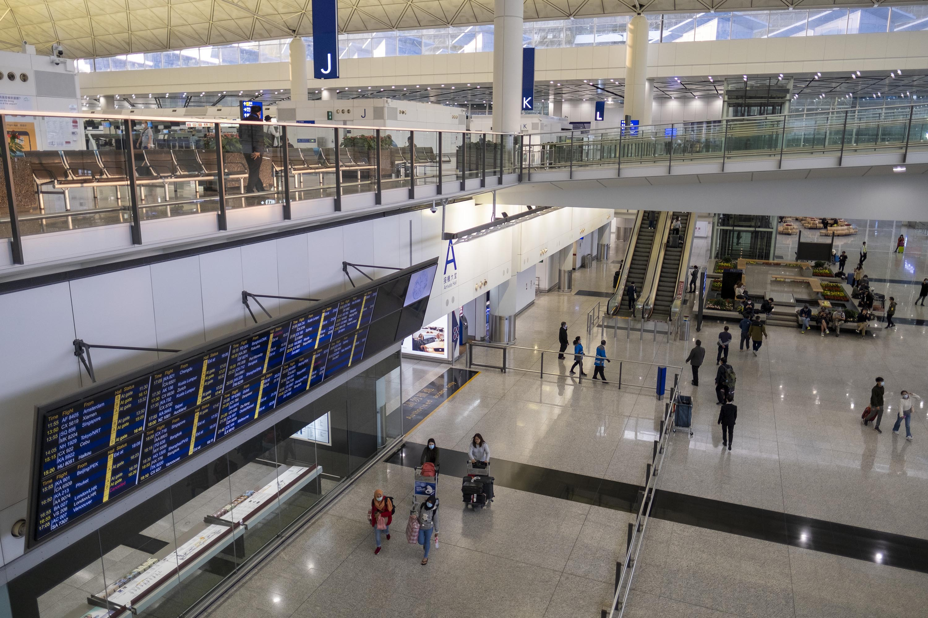 Travelers pass through the arrivals hall of Hong Kong International Airport on March 18.