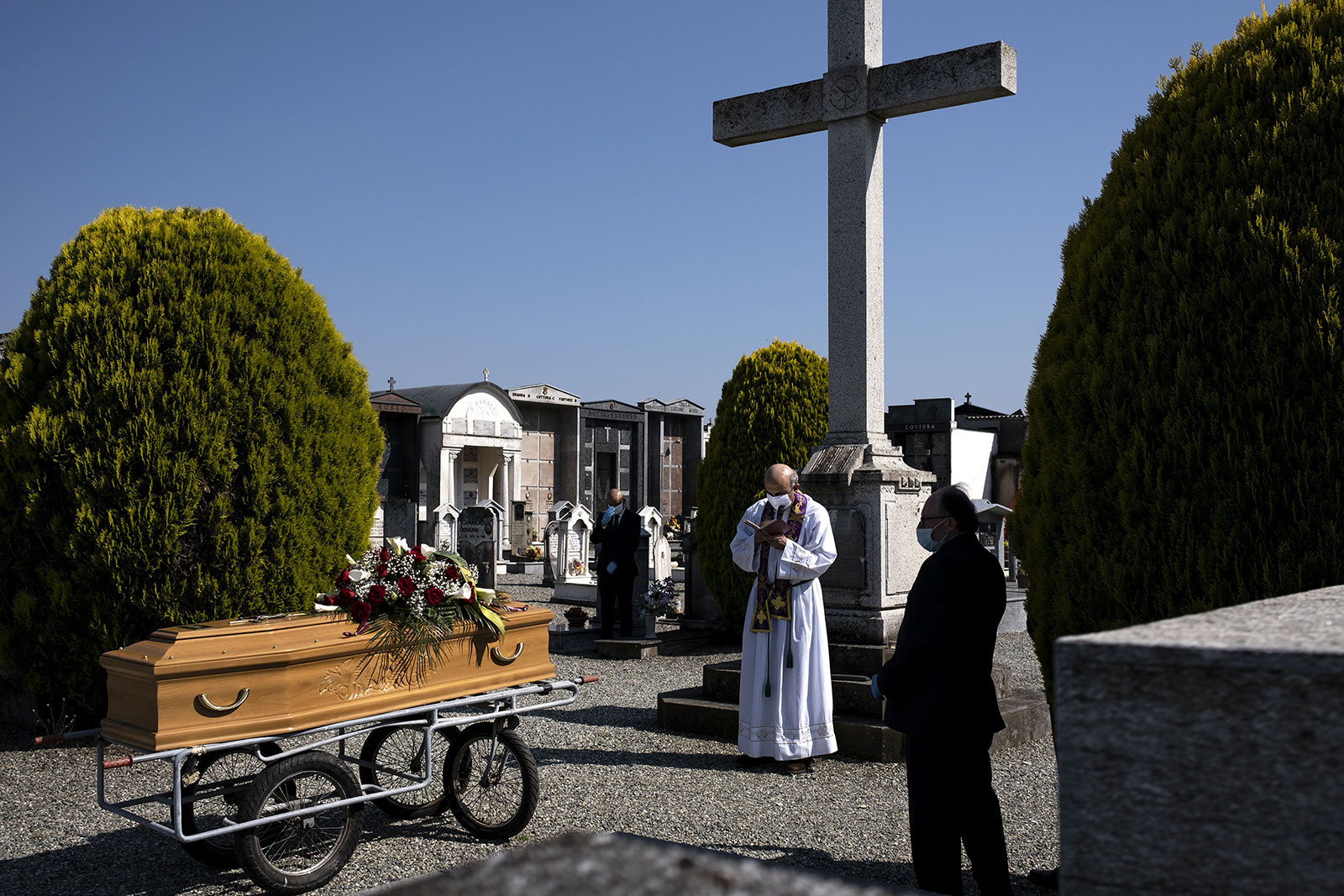 A priest conducts a funeral service for a coronavirus victim on April 24, in Cuneo, Italy.