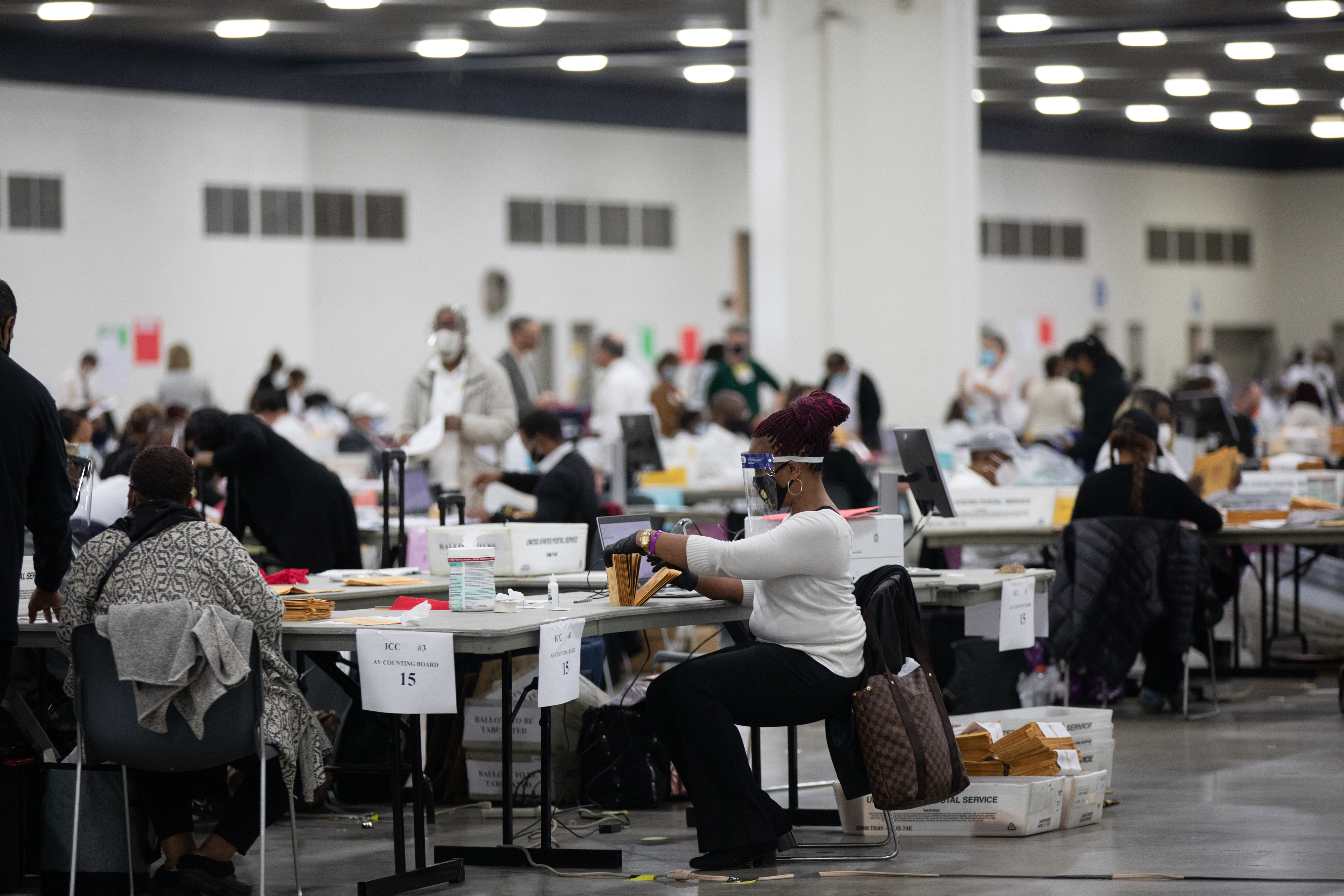 Volunteers wearing protective masks process absentee ballots for the 2020 Presidential election at the TCF Center in Detroit, Michigan on Nov. 3, 2020.
