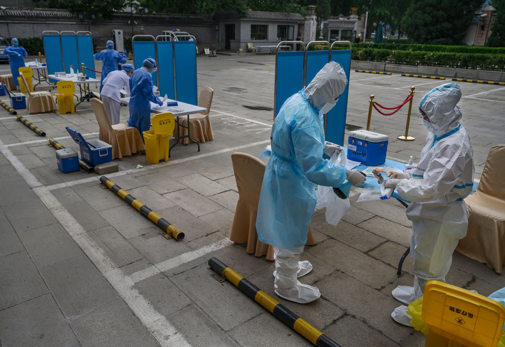 Chinese health workers sanitize safety equipment after carrying out nucleic acid tests in Beijing, China, on May 28.