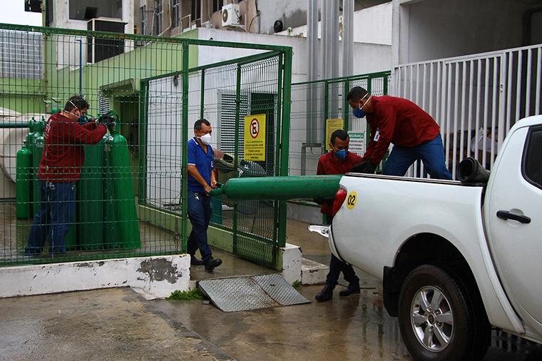 Amazonas Federal University's workers carry empty oxygen tanks at the Getulio Vargas Hospital amid the new coronavirus pandemic, Manaus, Brazil, Thursday, January 14.