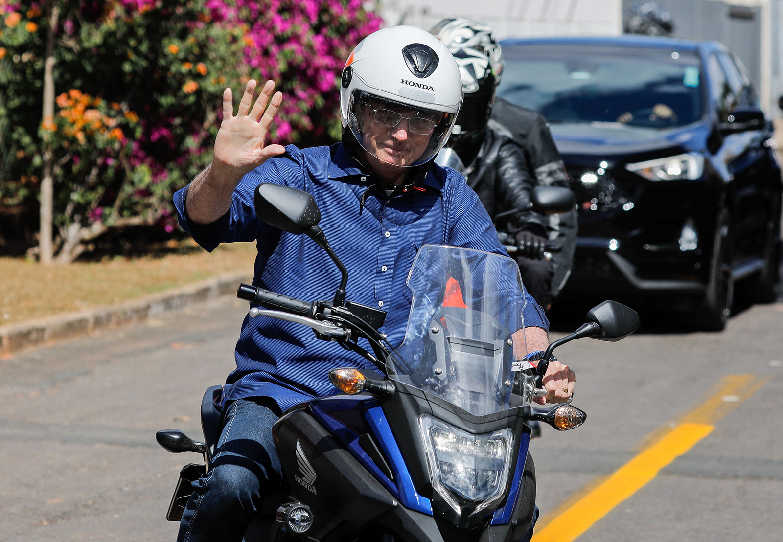 Brazilian President Jair Bolsonaro waves as he takes a ride in Brasilia, on July 25.