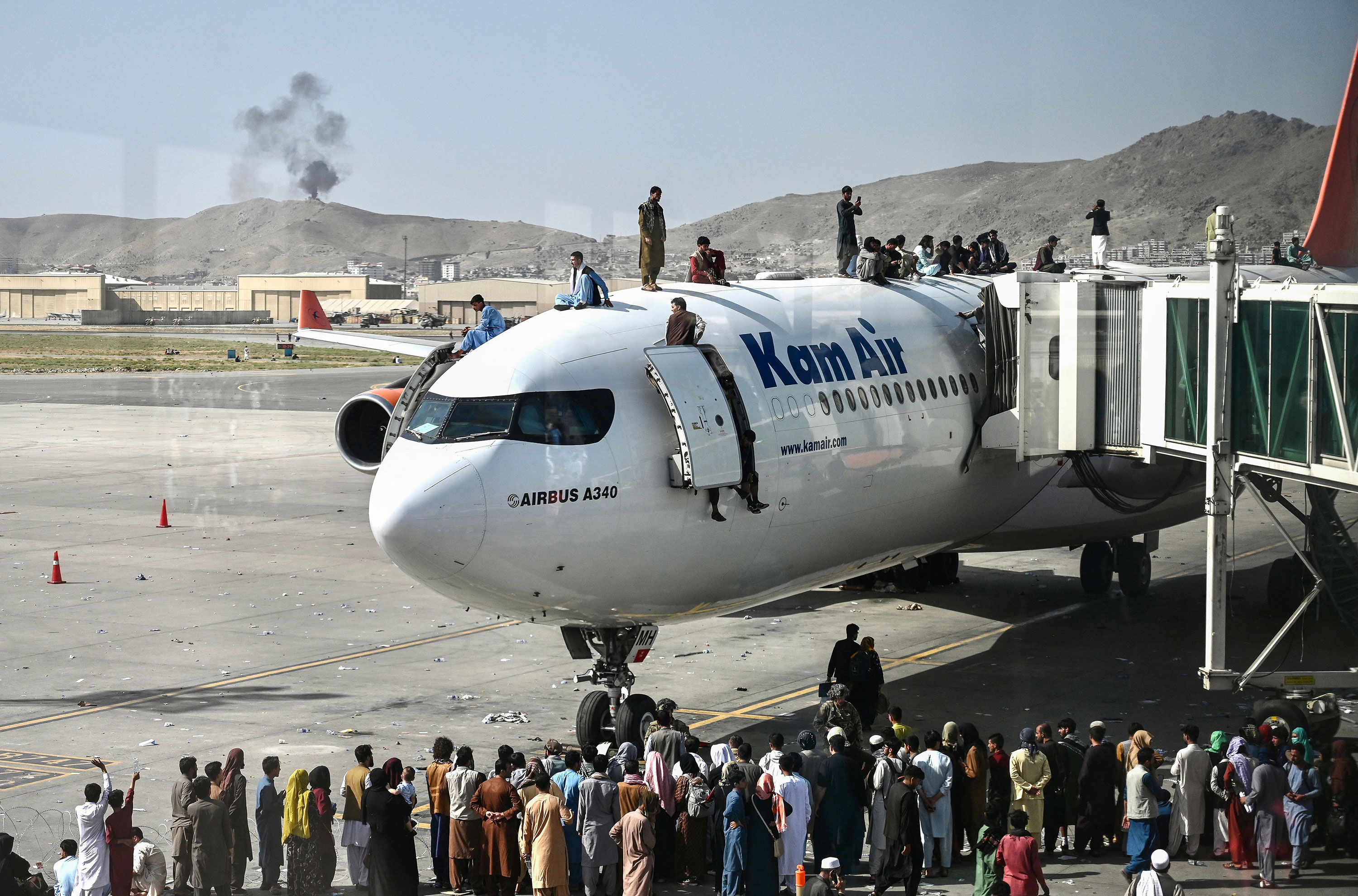 People climb atop a plane at the airport in Kabul on August 16.