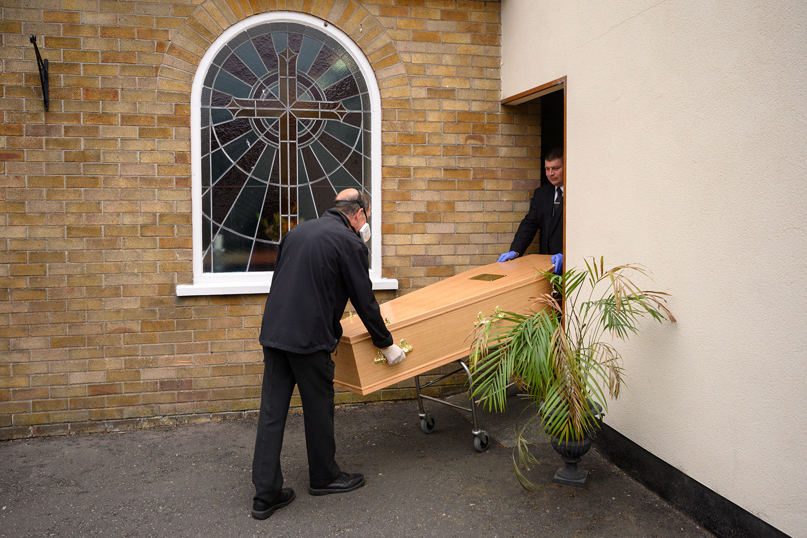 Funeral service workers load the coffin of a person who tested positive for Covid-19 into a hearse at their funeral home in Manchester, England on May 26.