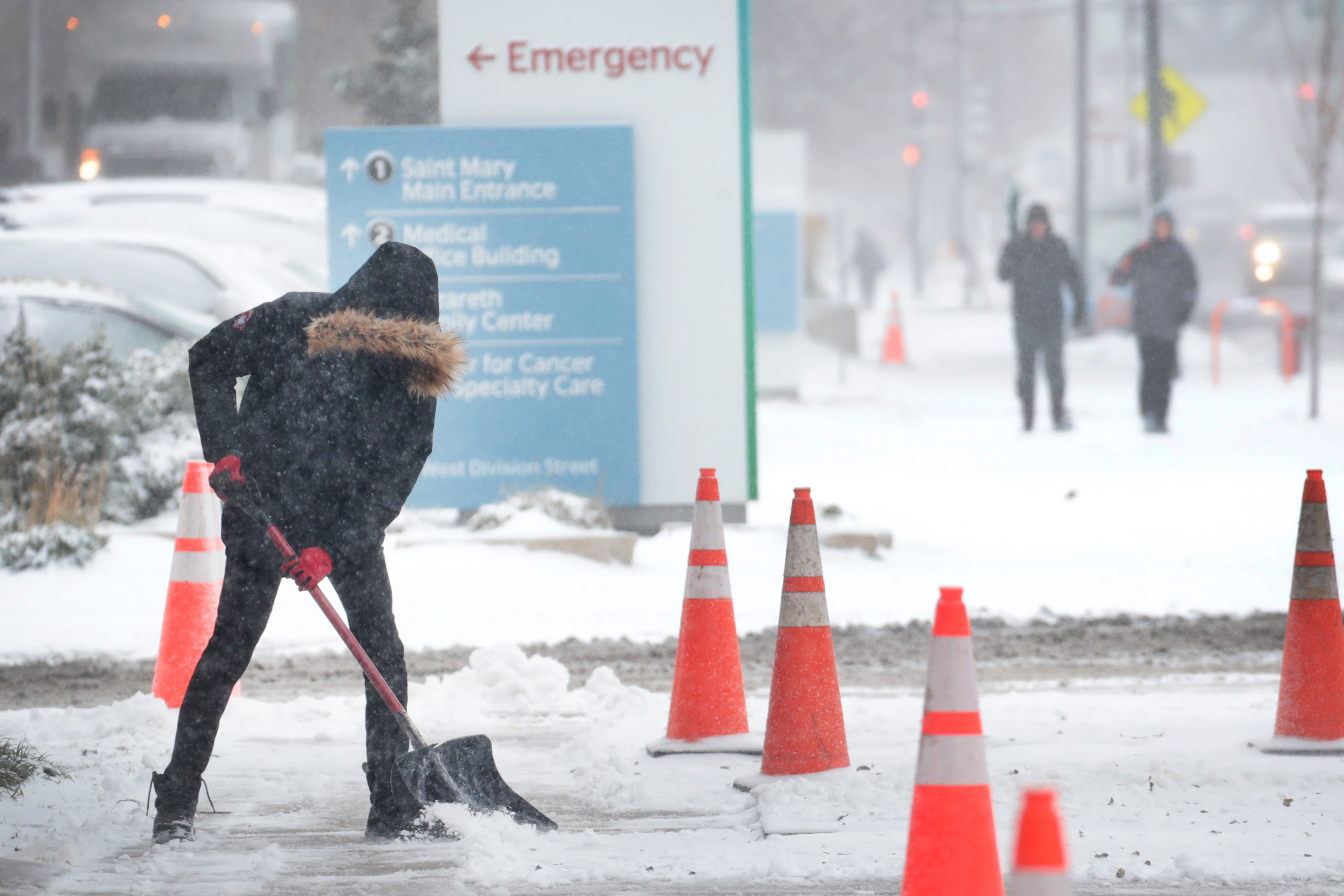 A worker shovels snow from a sidewalk in Chicago on Monday.