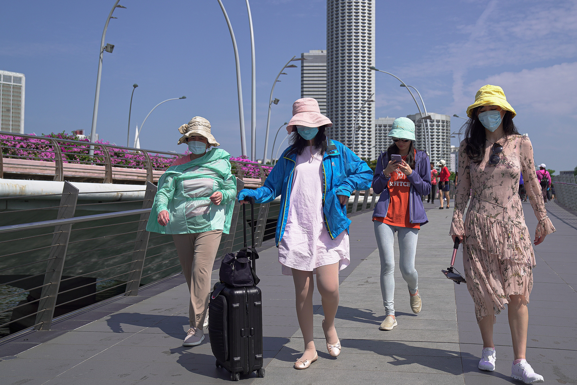 Visitors wearing masks walk through the Merlion Park on January 26 in Singapore.