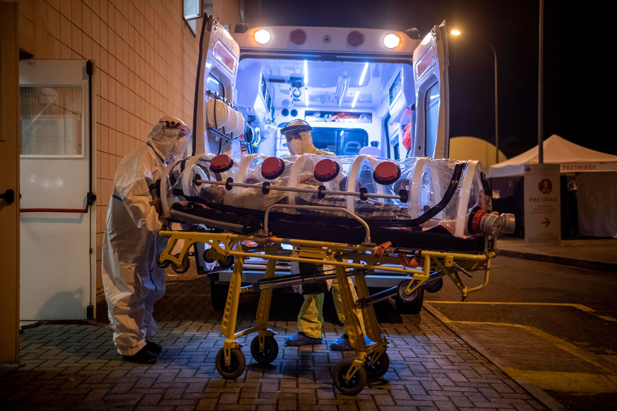 Healthcare workers transfer a COVID-19 patient in a biocontainment stretcher at the emergency room of San Filippo Neri Hospital on October 29 in Rome, Italy.
