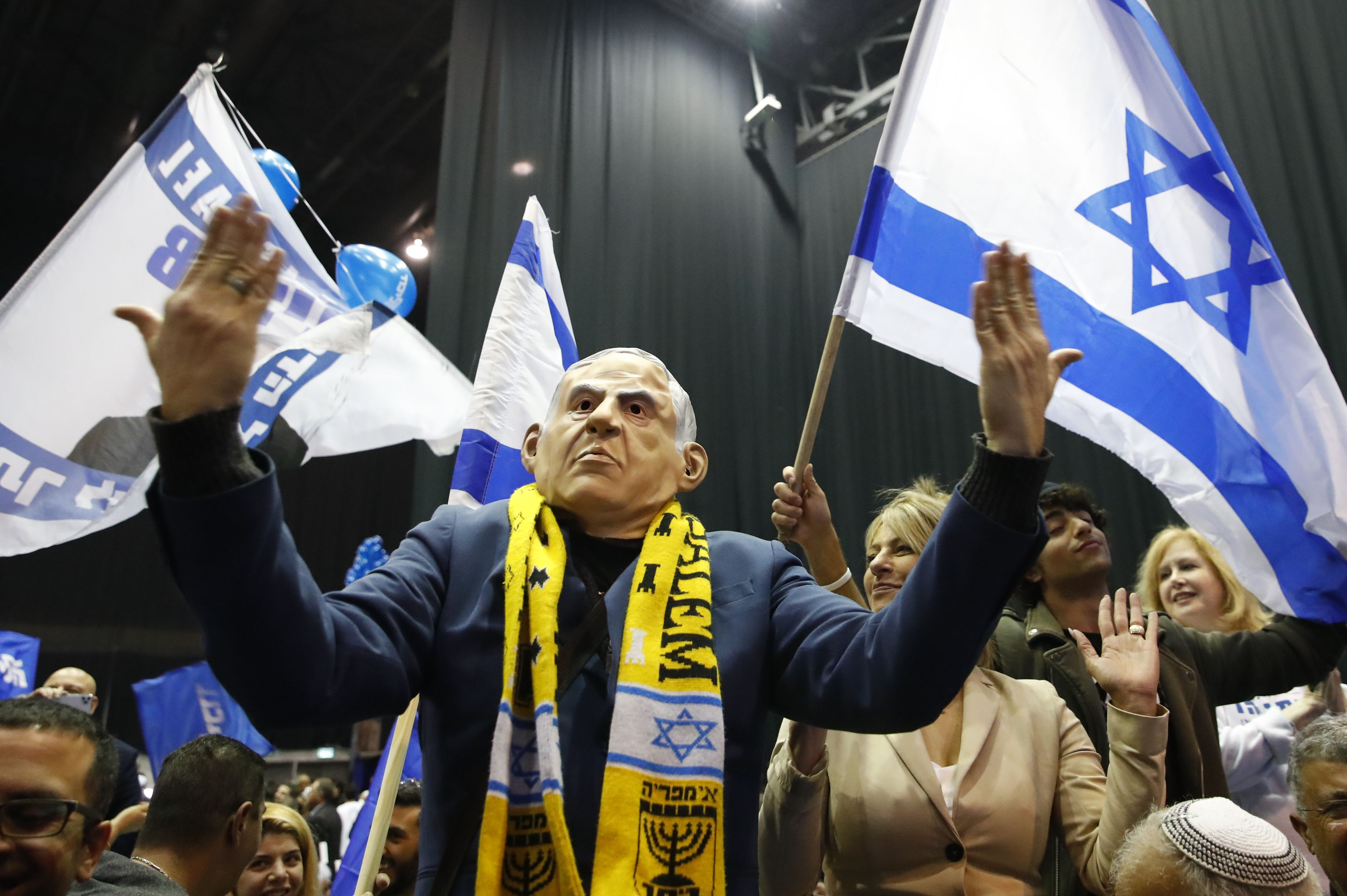 A man in a Benjamin Netanyahu face mask celebrates at the Likud's electoral headquarters. Jack Guez/AFP