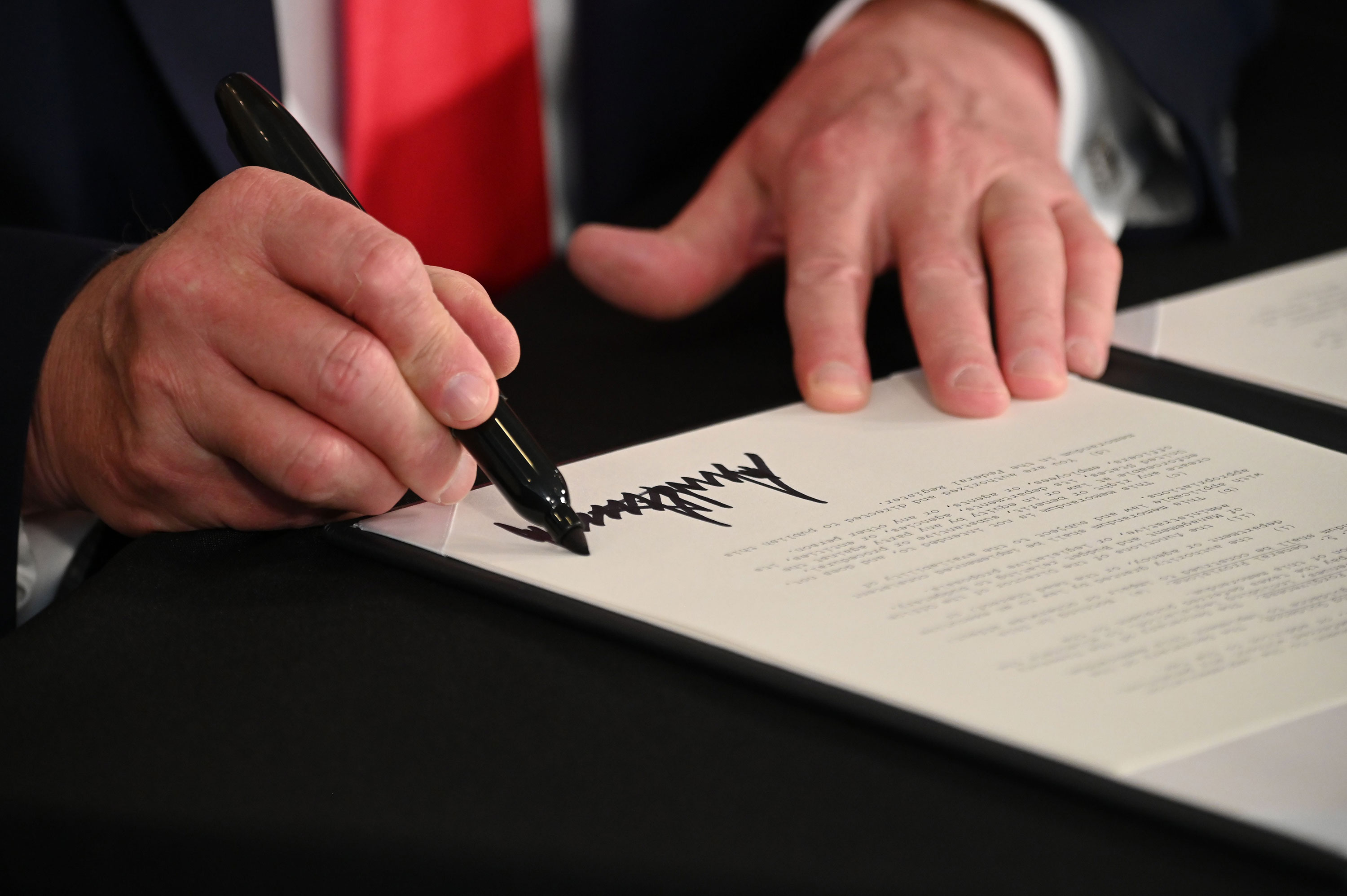 President Donald Trump signs executive orders during a news conference in Bedminster, New Jersey, on August 8.