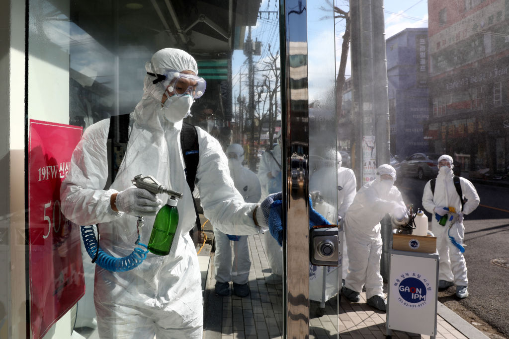 Workers spray antiseptic solution against the coronavirus in Seoul today.