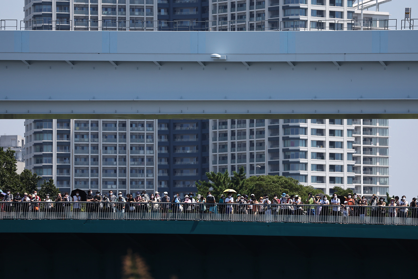 People watch the BMX freestyle event from a bridge in Tokyo on Sunday.