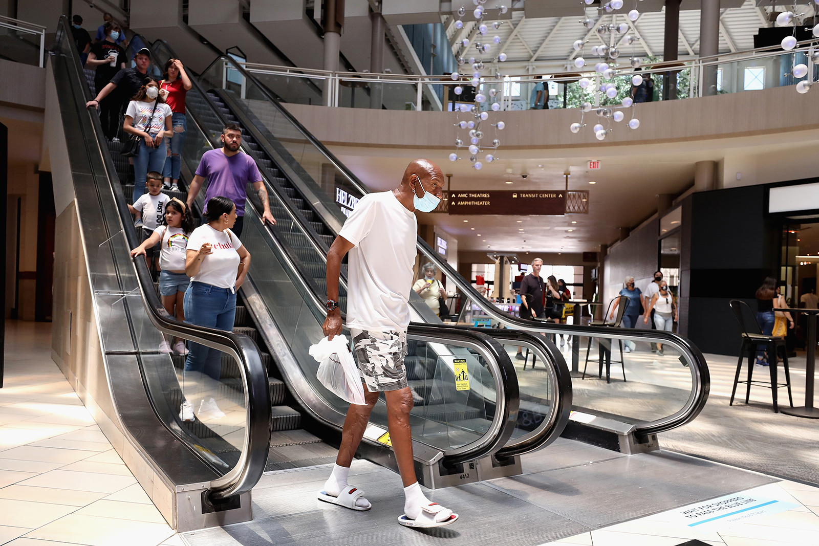Shoppers exit an escalator as they return to retail shopping at the Arrowhead Towne Center on June 20, in Glendale, Arizona.