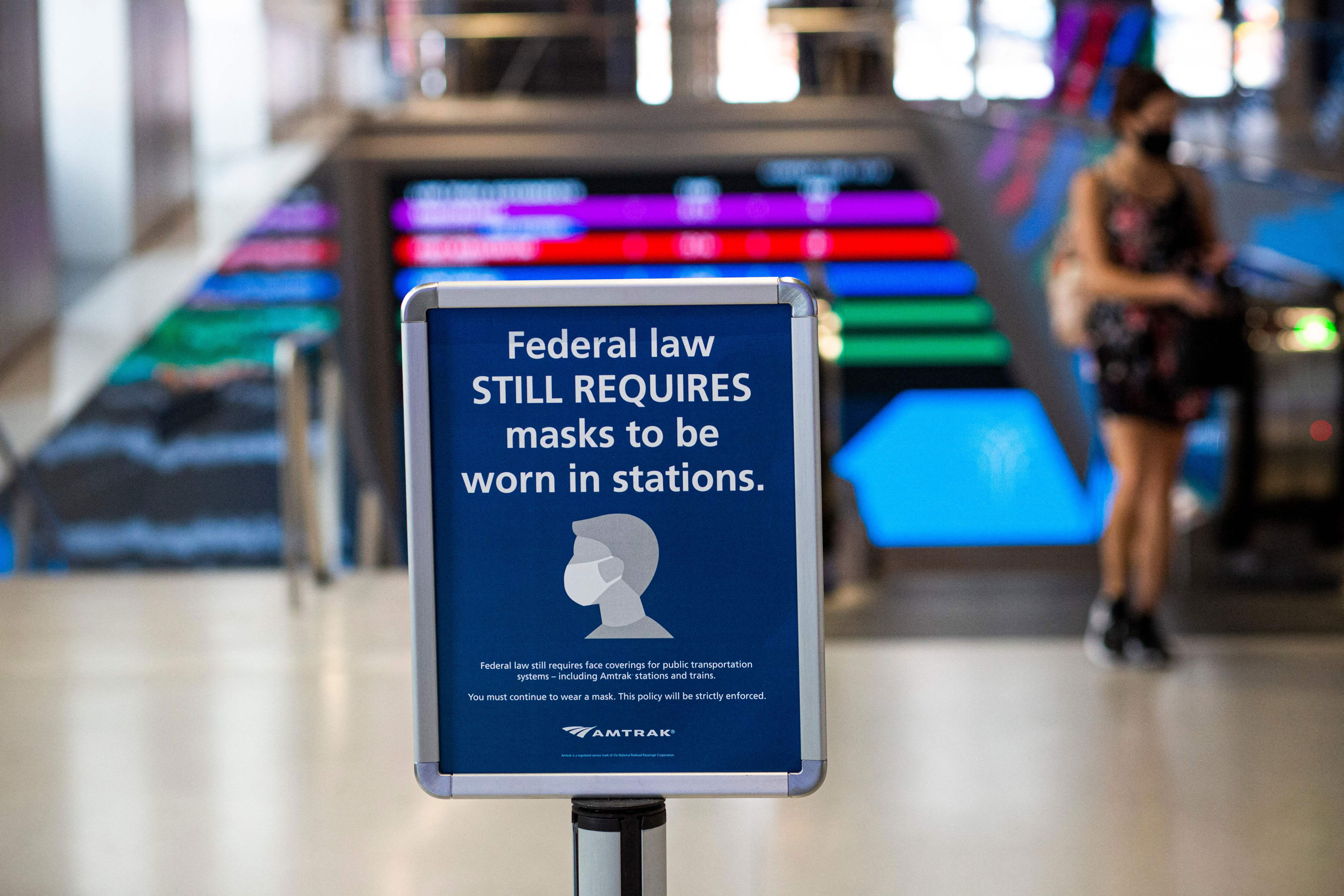 A woman walks past a sign calling for mask wearing at Penn Station in New York City, on August 2.