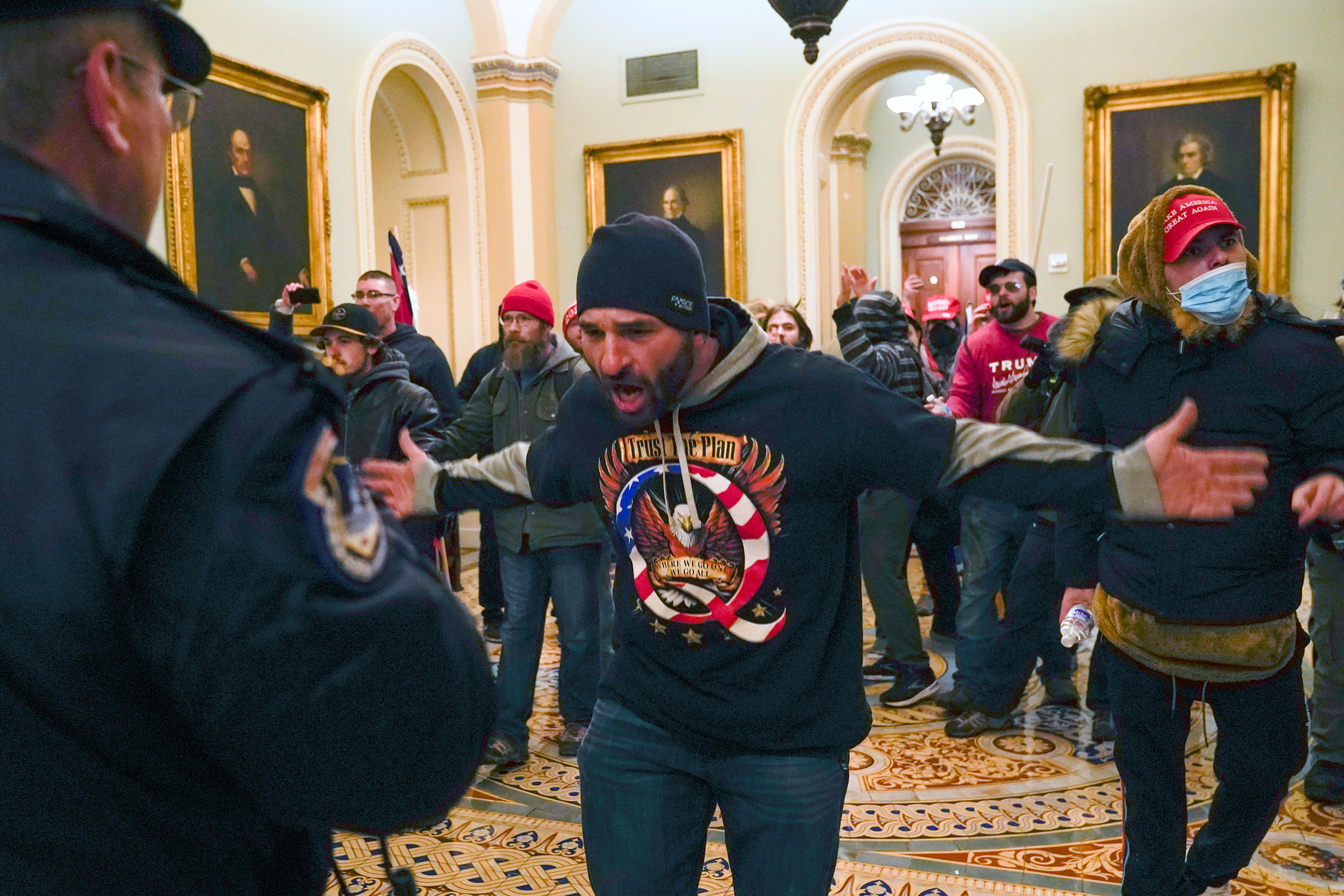 A supporter of President Donald Trump gestures to Capitol Police in the hallway outside of the Senate Chamber on January 6.