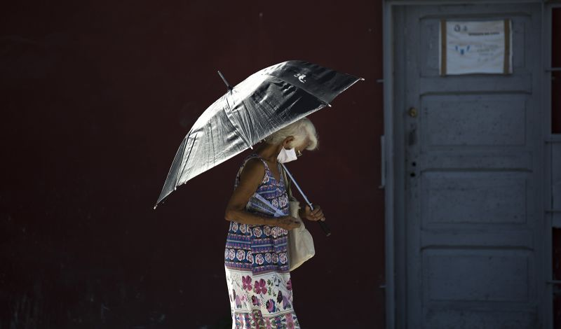 A pedestrian wearing a face mask amid the coronavirus pandemic uses a parasol in Havana, Cuba, on Monday, August 10.