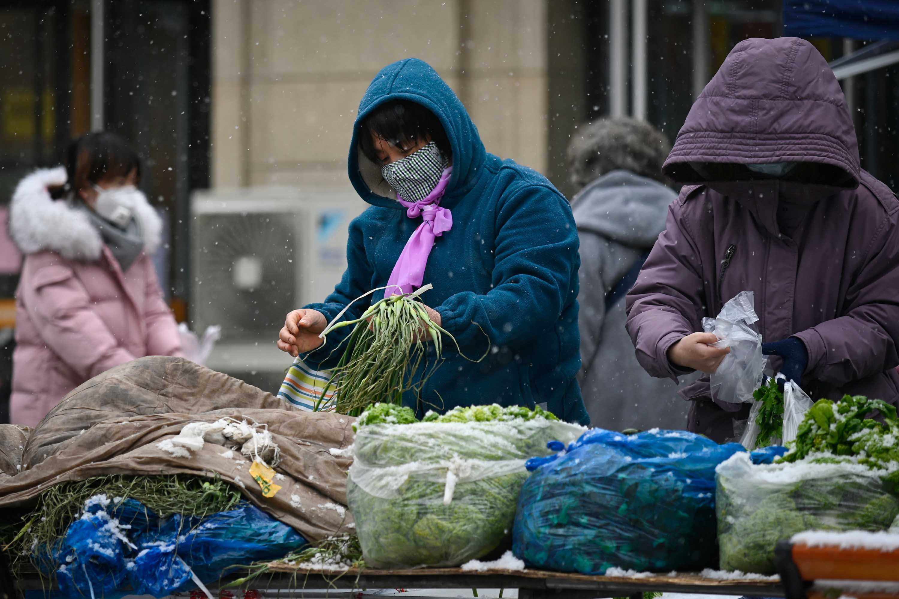People shop for vegetables at a market in Beijing on February 2.