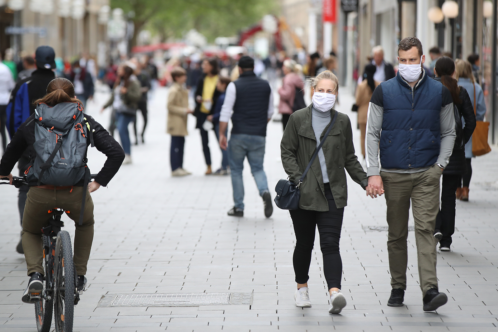 People wearing protective face masks walk on the main shopping street in Munich City during the coronavirus crisis on April 30, in Munich, Germany.