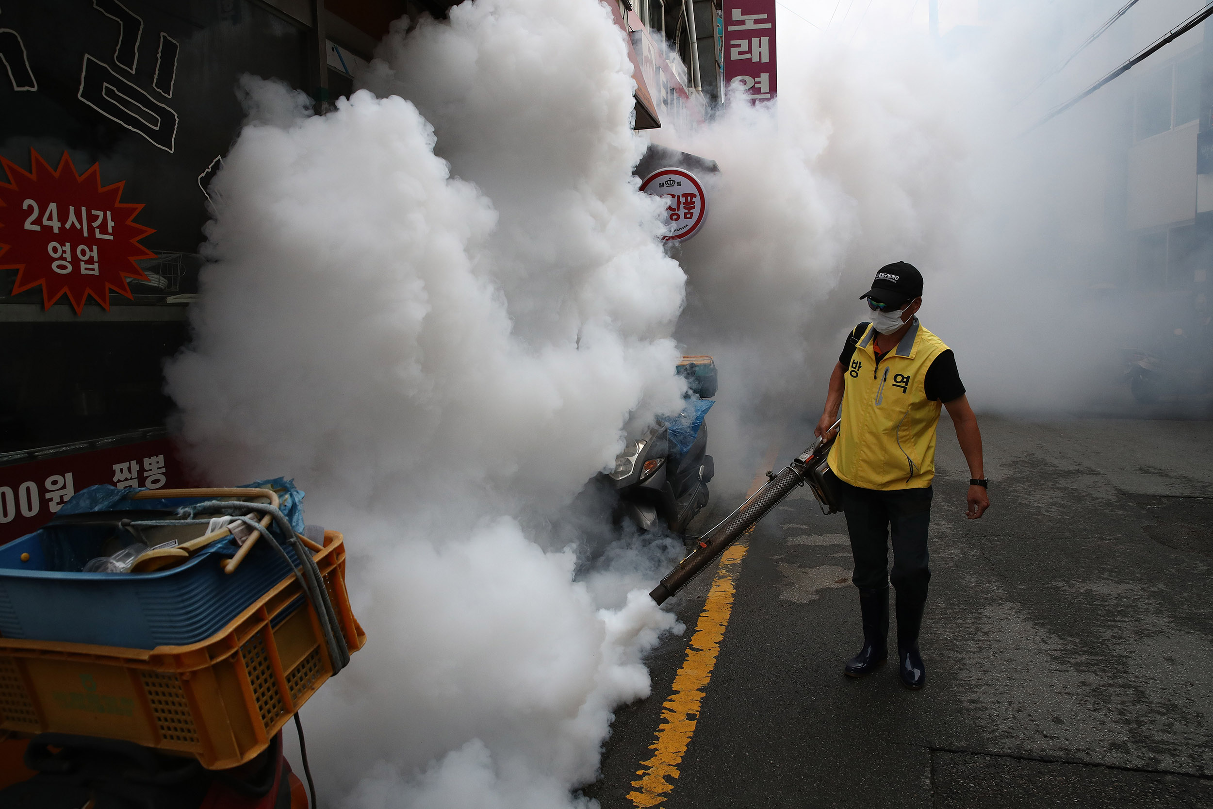 A worker disinfects an alley in in Seoul, South Korea, to prevent the spread of coronavirus on Saturday, August 29.