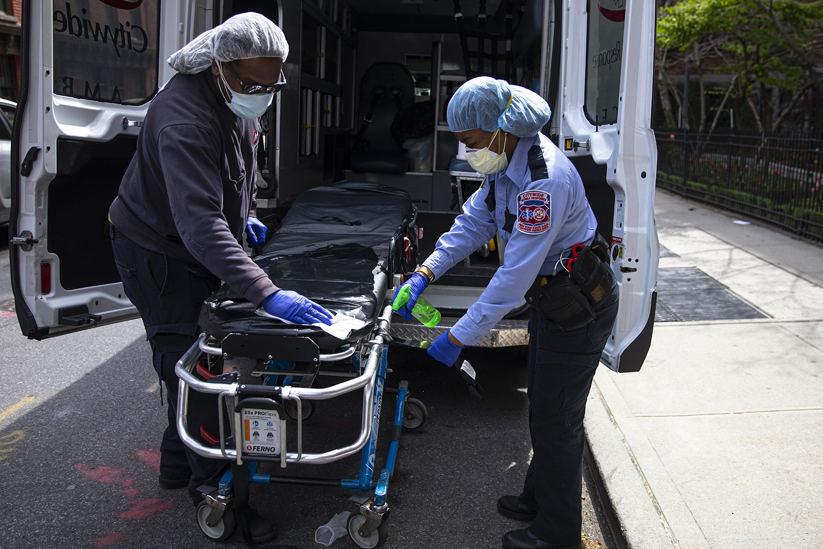 Two emergency medical staff of a private ambulance company sanitize a hospital gurney after they dropped off a patient at the Cobble Hill Health Center April 20, 2020 in the Brooklyn borough of New York City.
