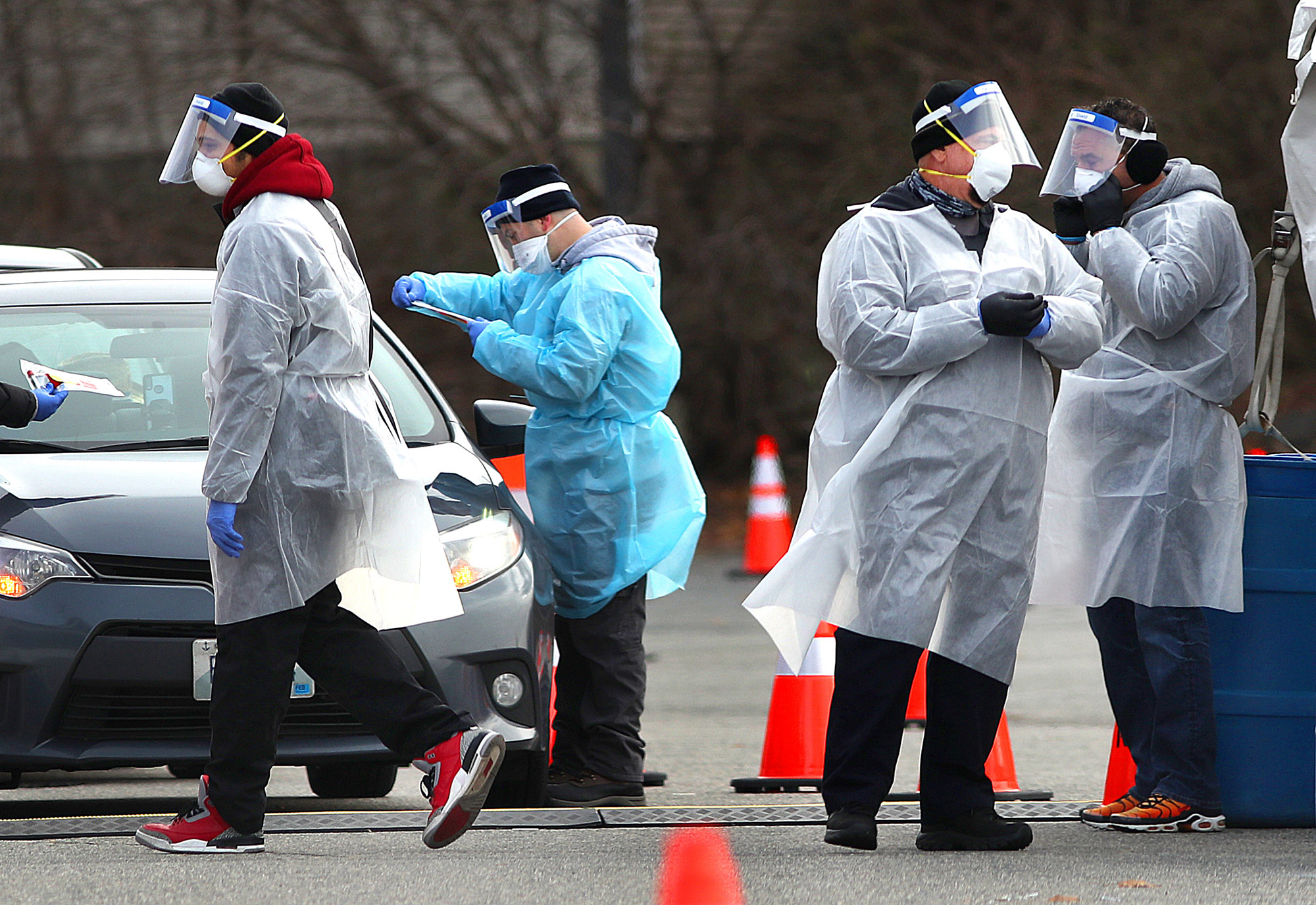 Health care workers on hand as they administer COVID-19 tests in the parking lot at McCoy Stadium in Pawtucket, Rhode Island on December 8.