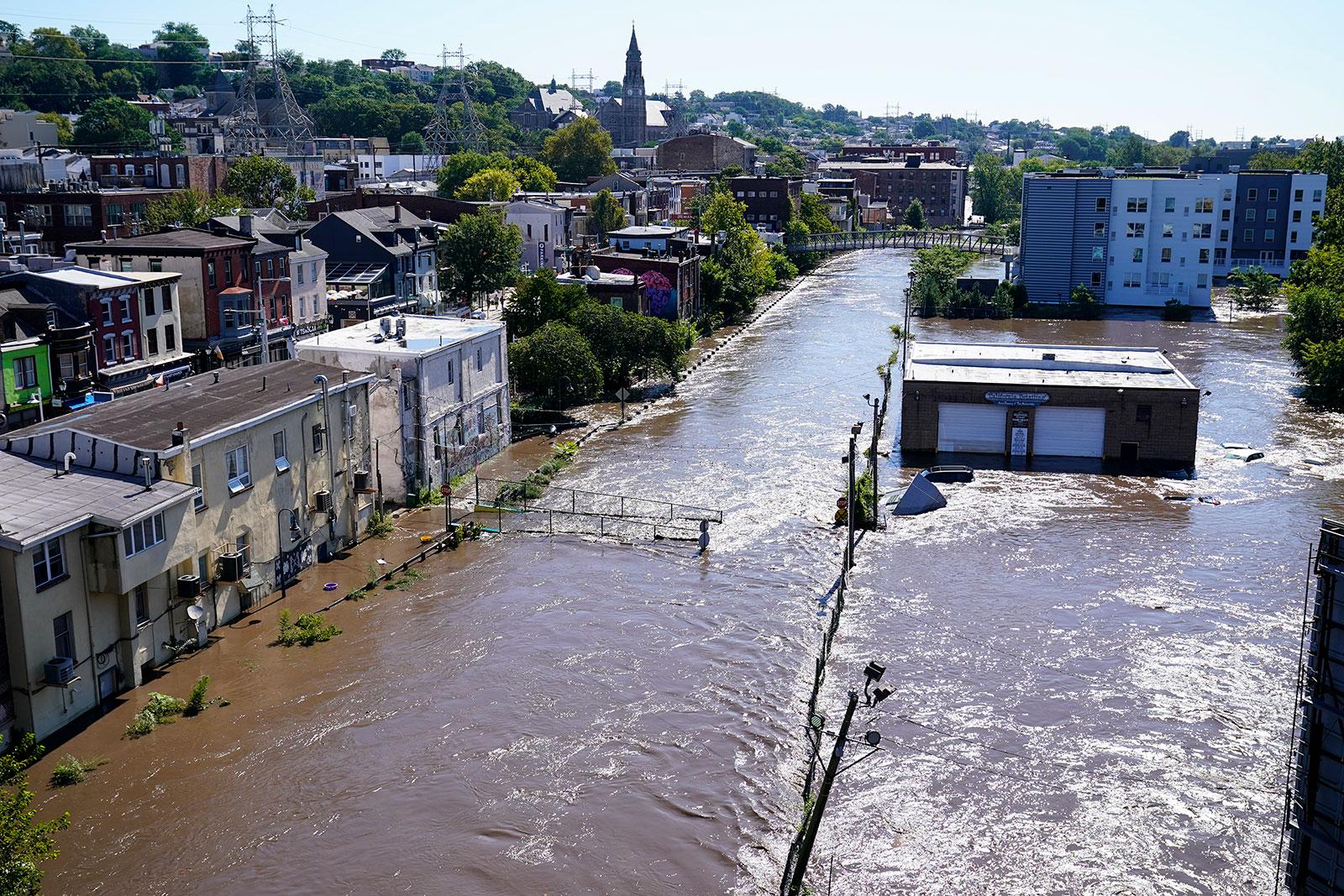 Water spills over the banks of the Schuylkill River in Philadelphia on Thursday.