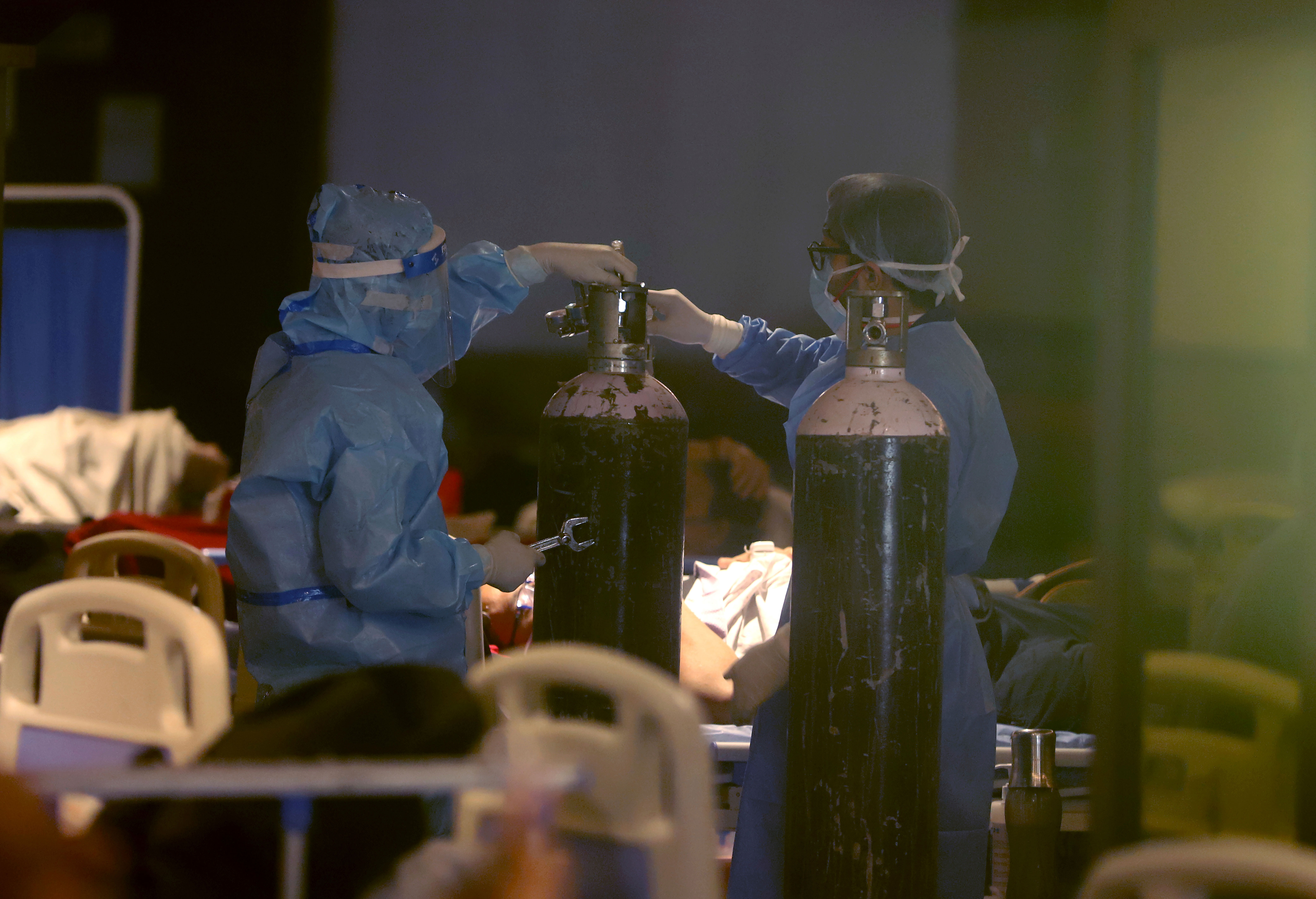 Health workers install oxygen cylinders for Covid-19 patients at a makeshift hospital in New Delhi on April 30.