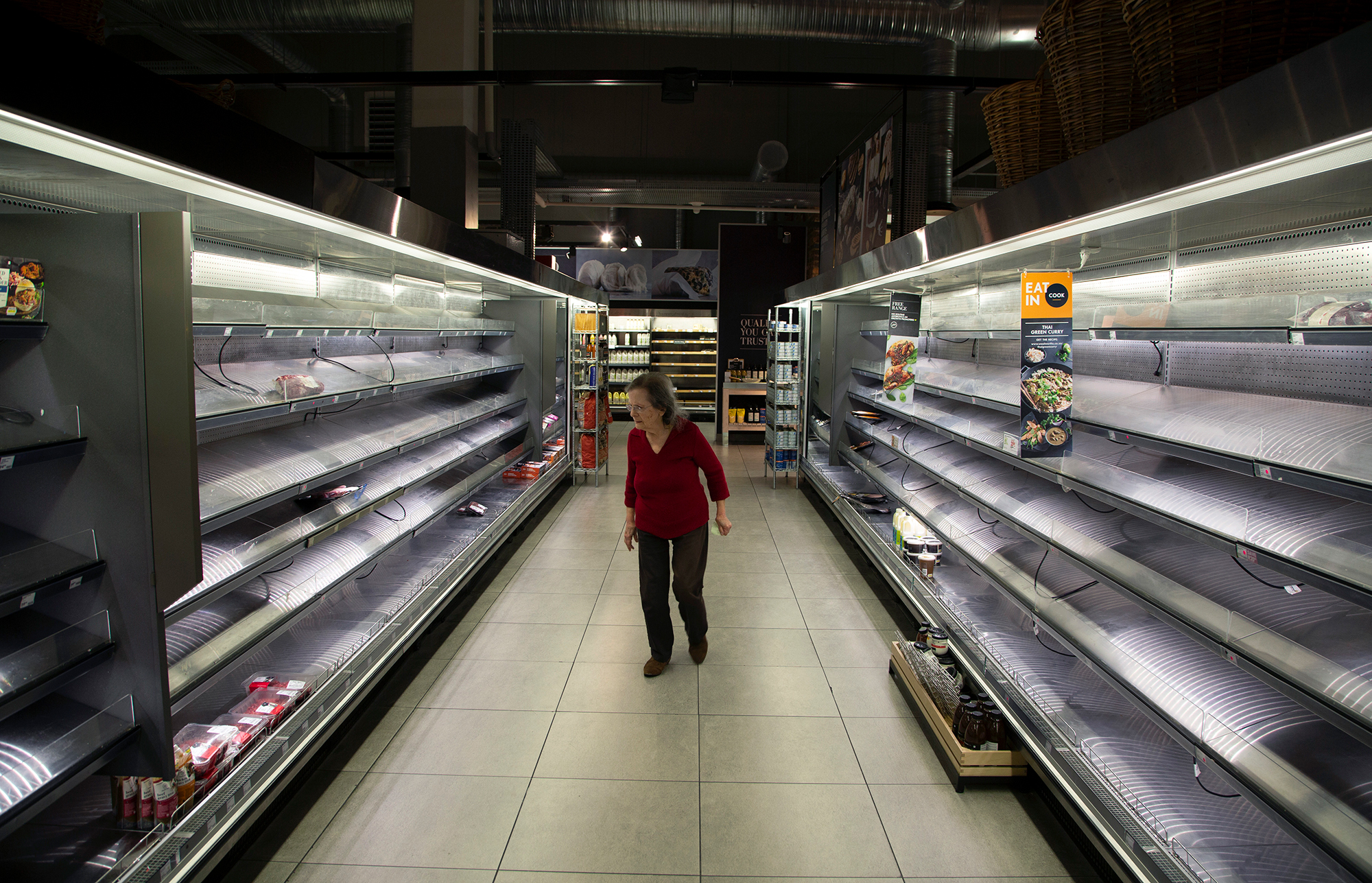 A woman looks at the few items left in the fresh meat and poultry fridges in a Johannesburg supermarket, Wednesday, March 18, amid panic-buying due to the coronavirus outbreak.