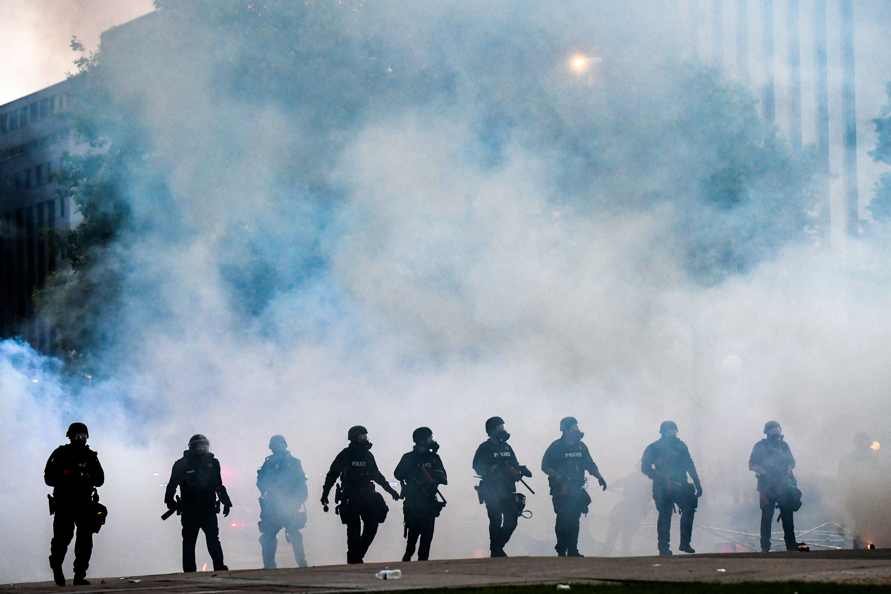 Police officers walk through a cloud of tear gas as they try to disperse protesters on May 30 in Denver, Colorado.