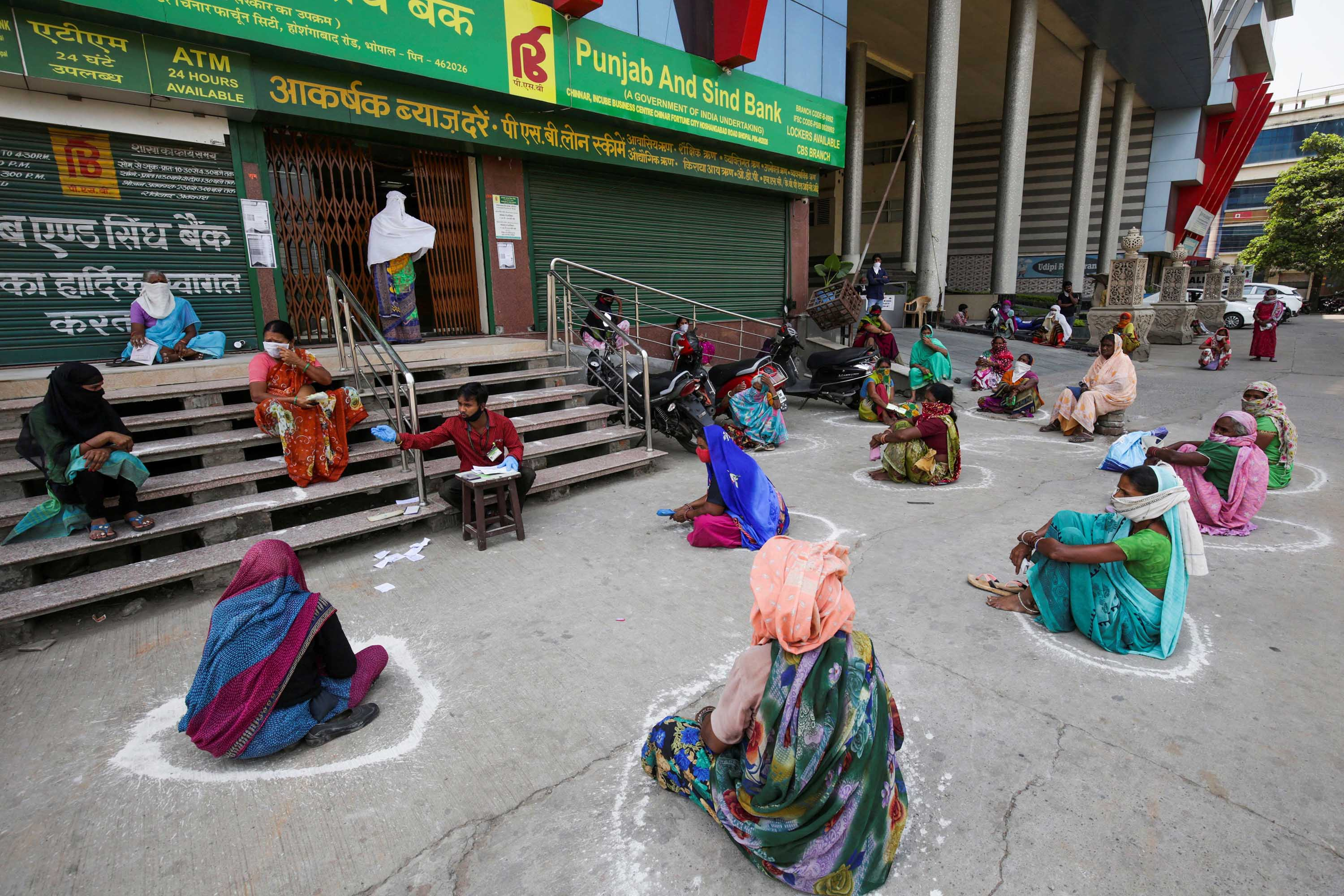Women maintain social distancing outside a bank in Bhopal, in the Indian state of Madhya Pradesh, on April 15.
