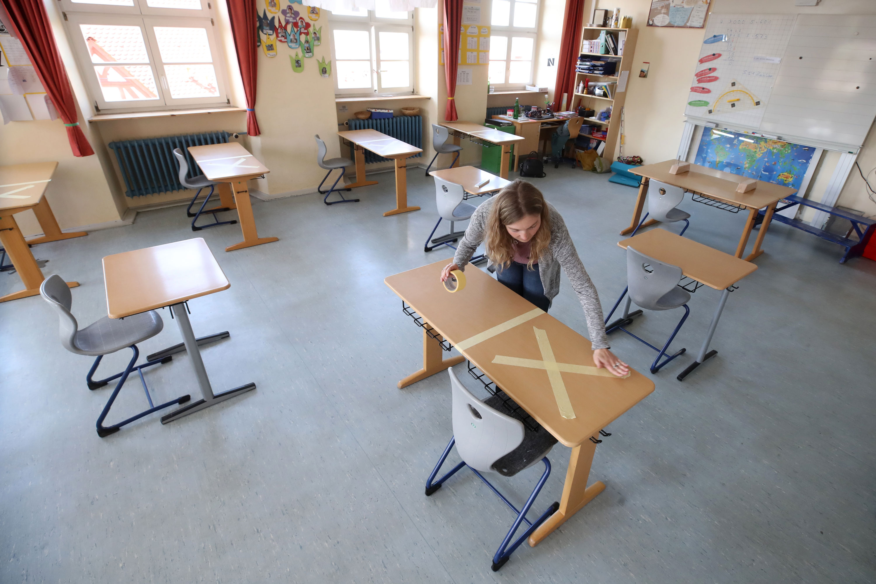 A staff member tapes social distancing markings during preparations for reopening a temporarily closed elementary school in Heppenheim, Germany, on April 21, 2020.