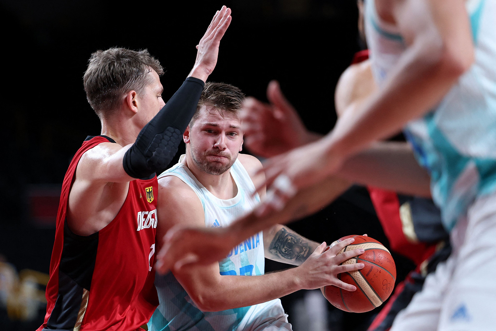 Slovenia's Luka Doncic dribbles past German players in the men's quarter-finals match on Tuesday.