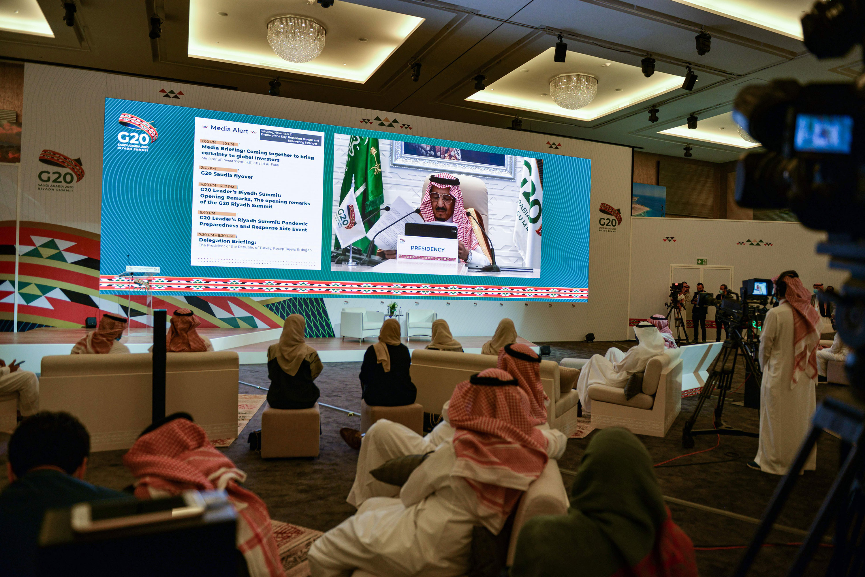 Members of the media watch on a projected screen at the International Media Centre in Saudi Arabia