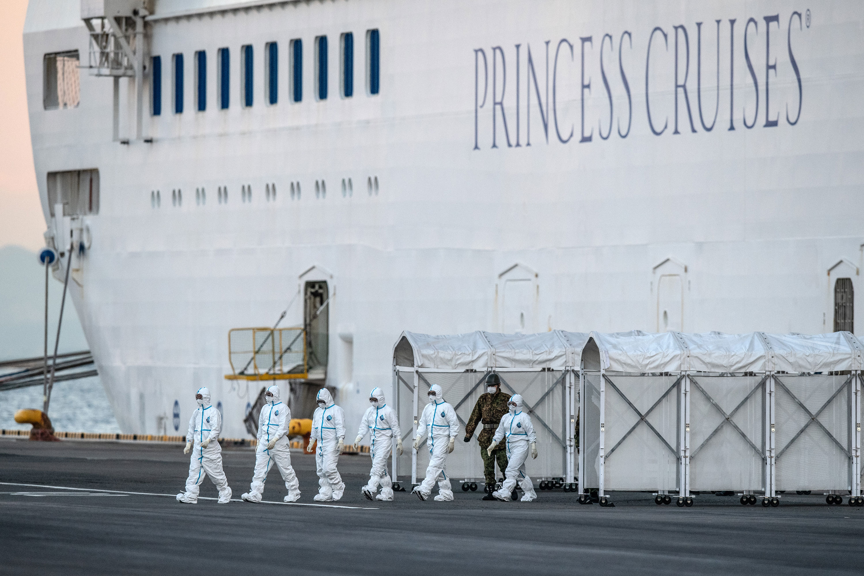 Emergency workers in protective clothing exit the Diamond Princess cruise ship at Daikoku Pier in Yokohama, Japan, on February 10.