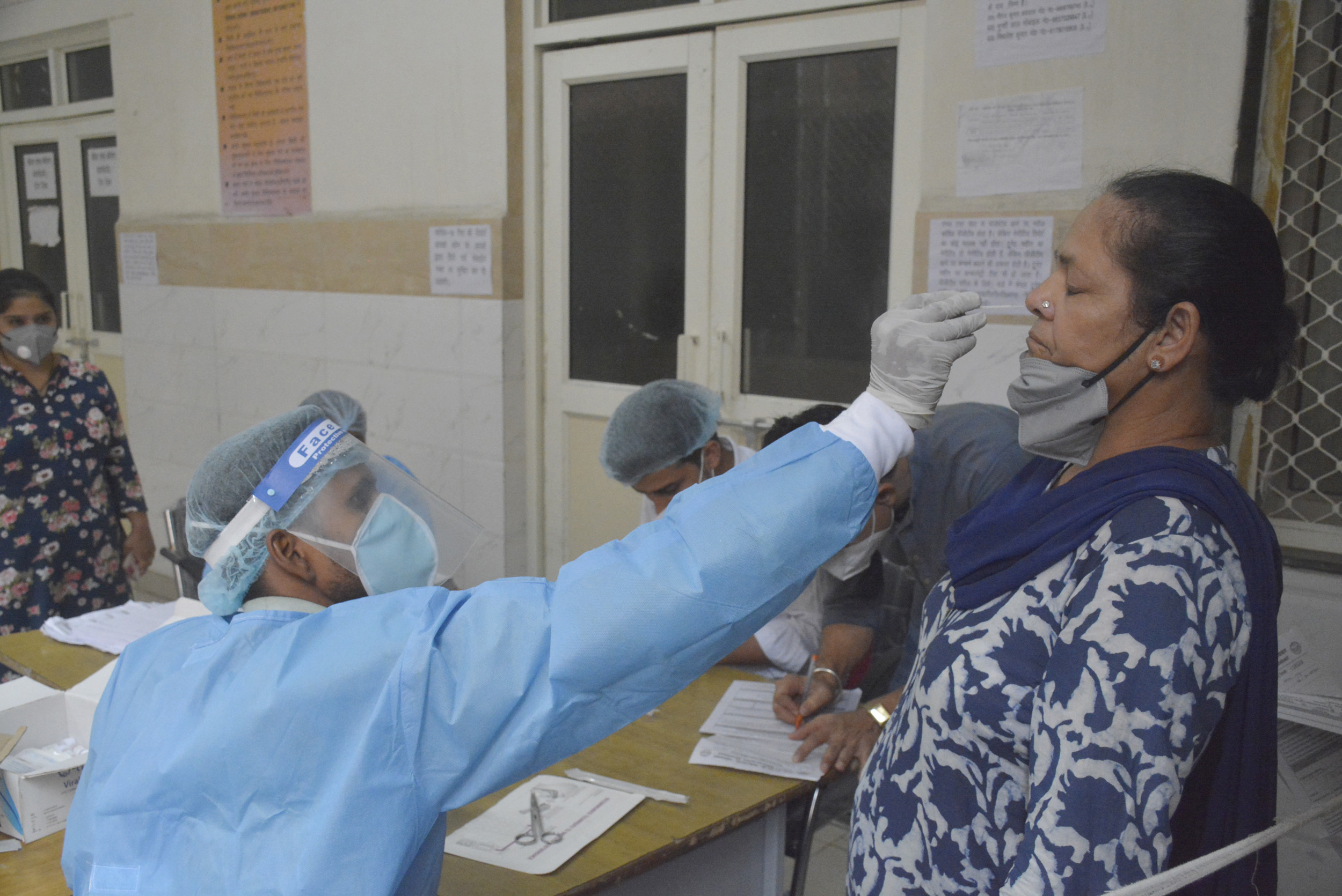 A medical professional collects swab sample to test for Covid-19 infection, at MMG hospital, on July 11, in Ghaziabad, India.