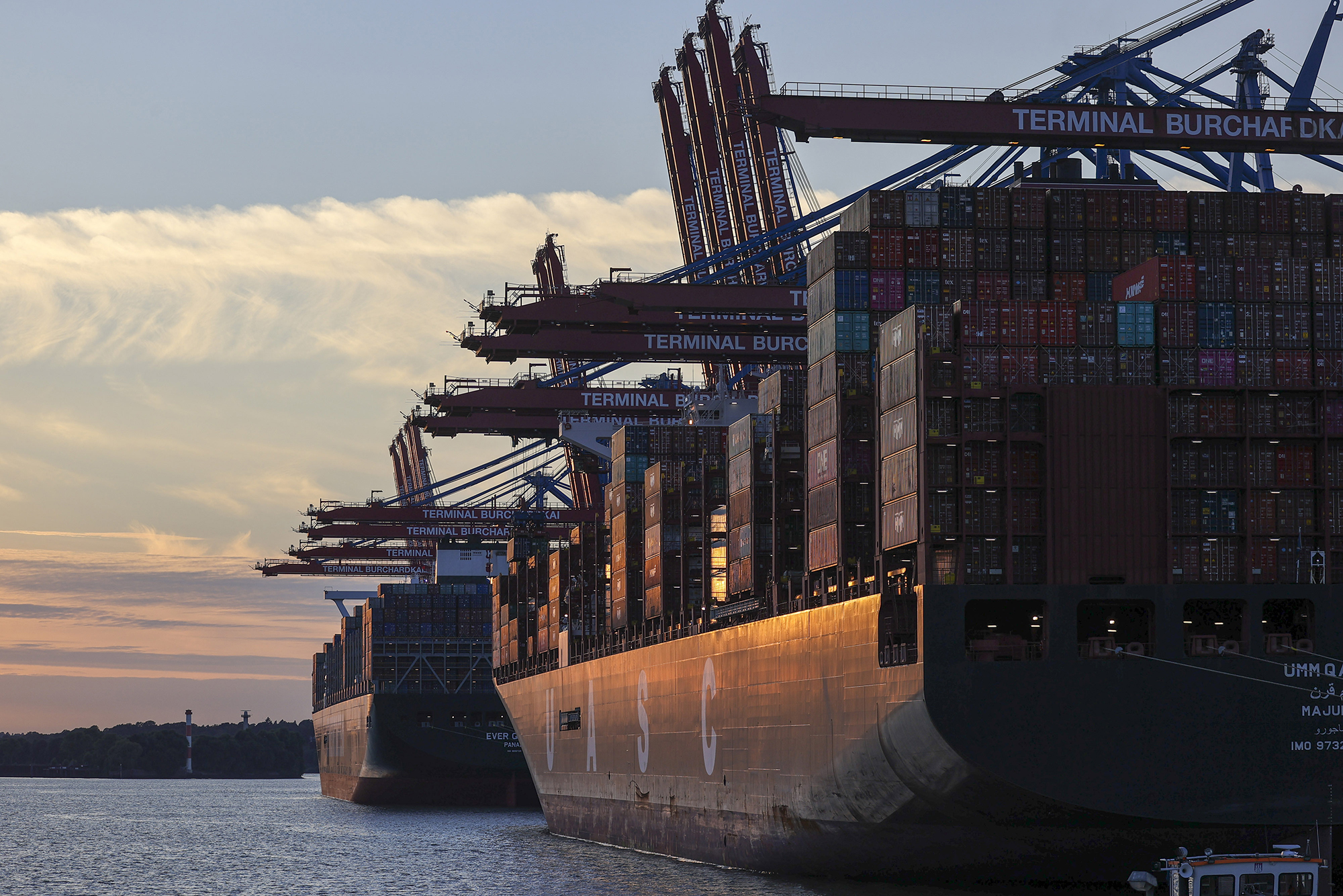 Shipping vessels from Evergreen Marine Corp and  Hapag-Lloyd AG sit docked at the HHLA Container Terminal Burchardkai at the Port of Hamburg on August 5 in Hamburg, Germany.