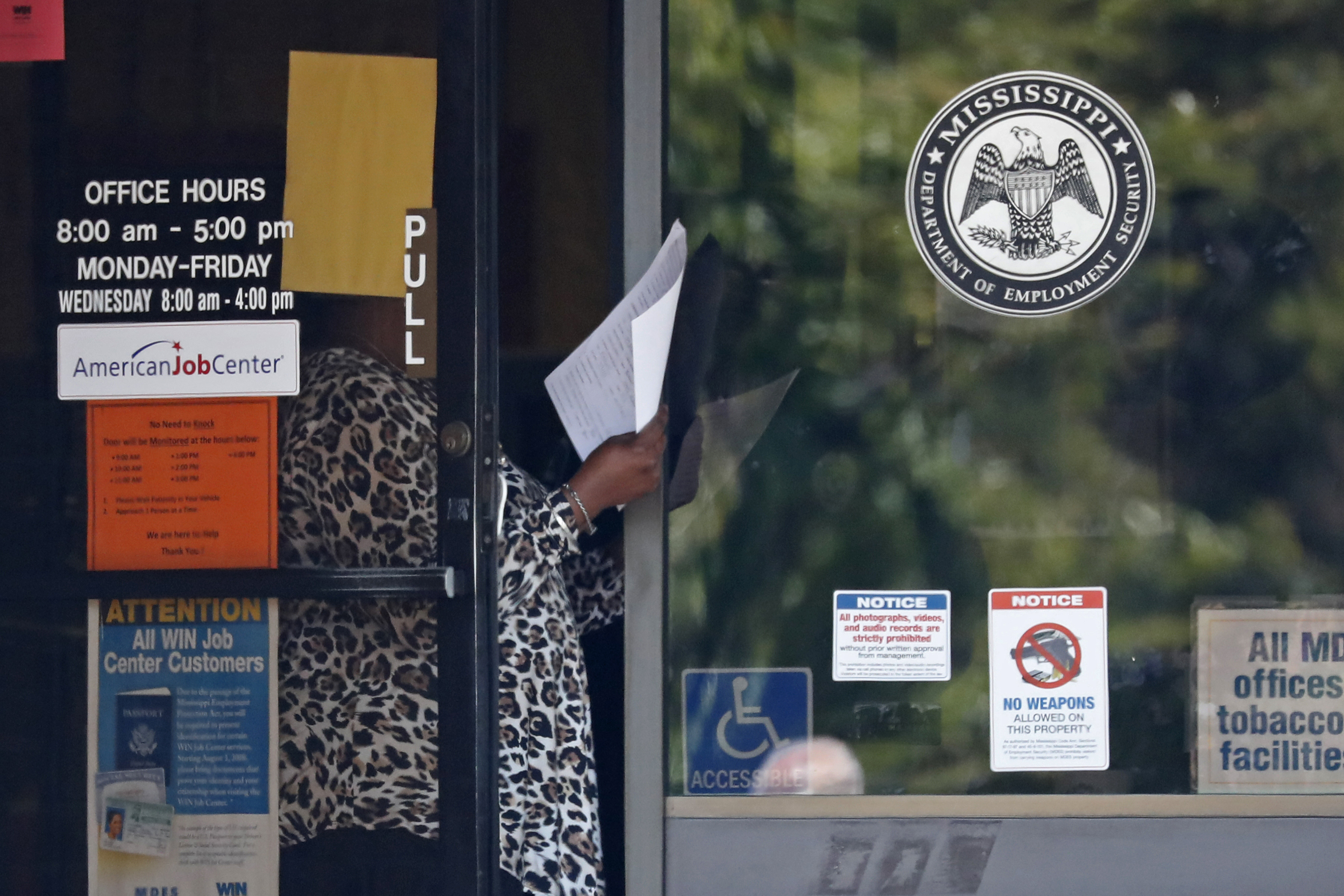 A worker at a WIN job center in Pearl, Mississippi, holds an unemployment benefits application form as she waits for a client on April 21.