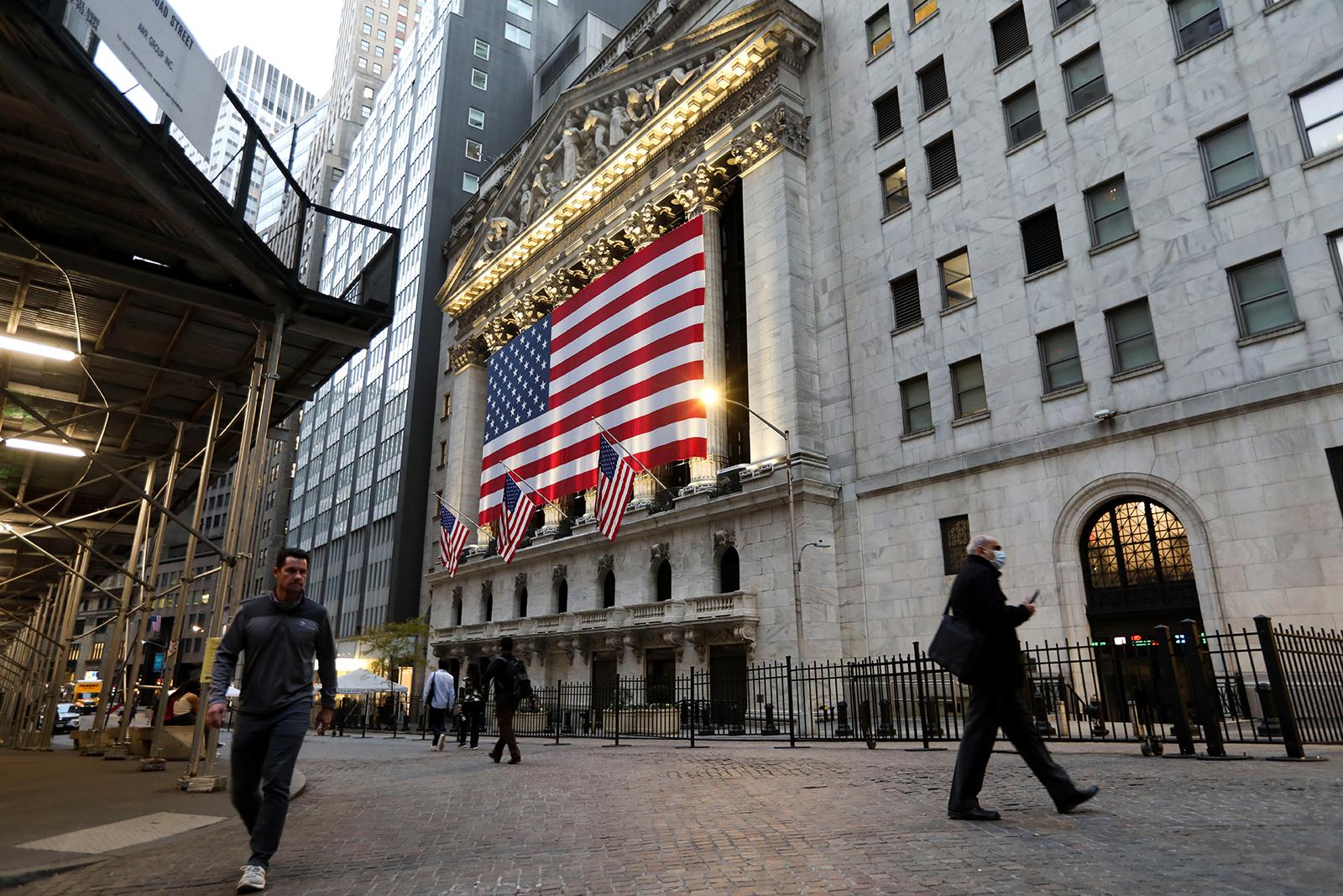 Pedestrians walk past the New York Stock Exchange in New York City, on Monday, November 9